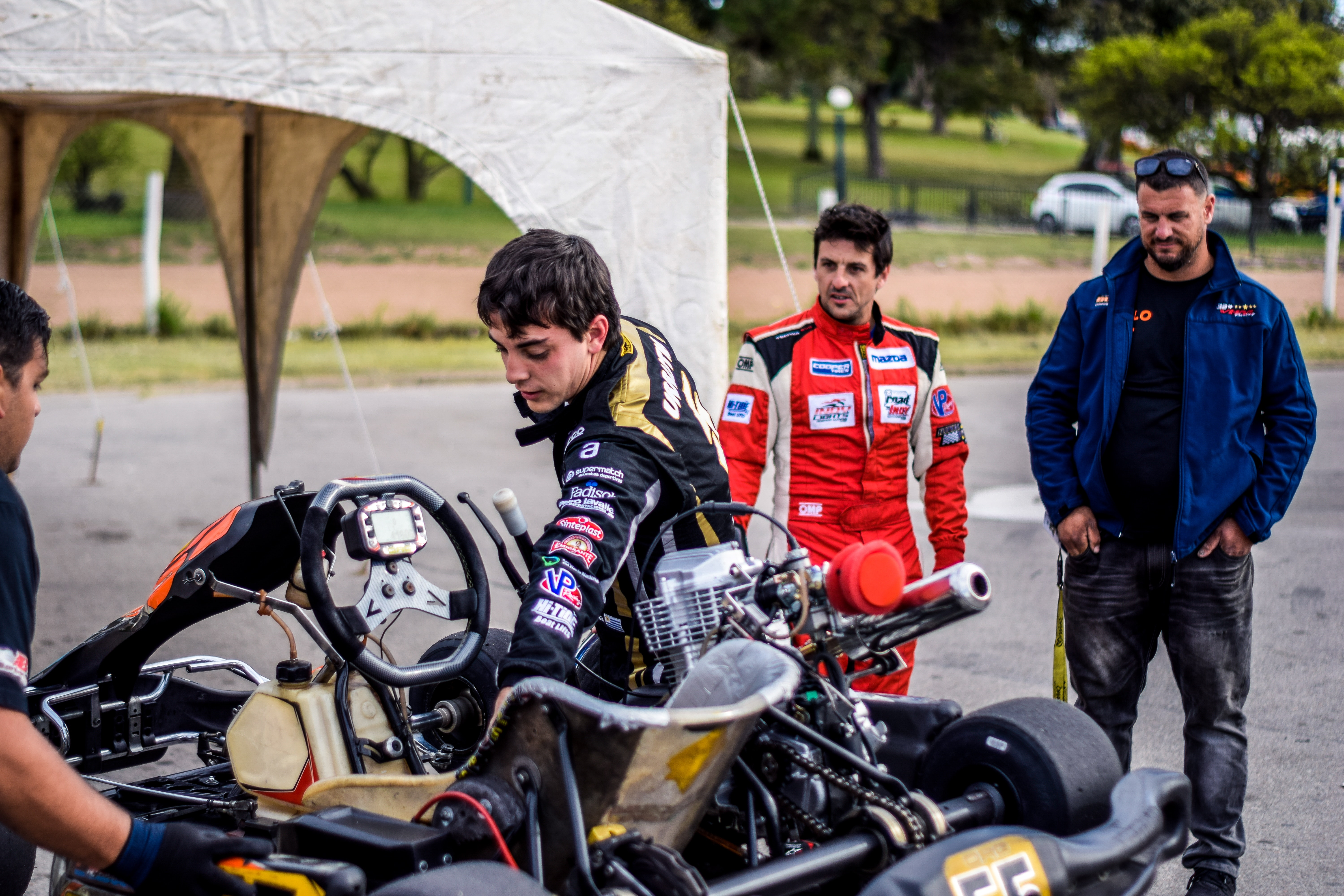 Two motorcycle racers standing in front of motorcycles photo
