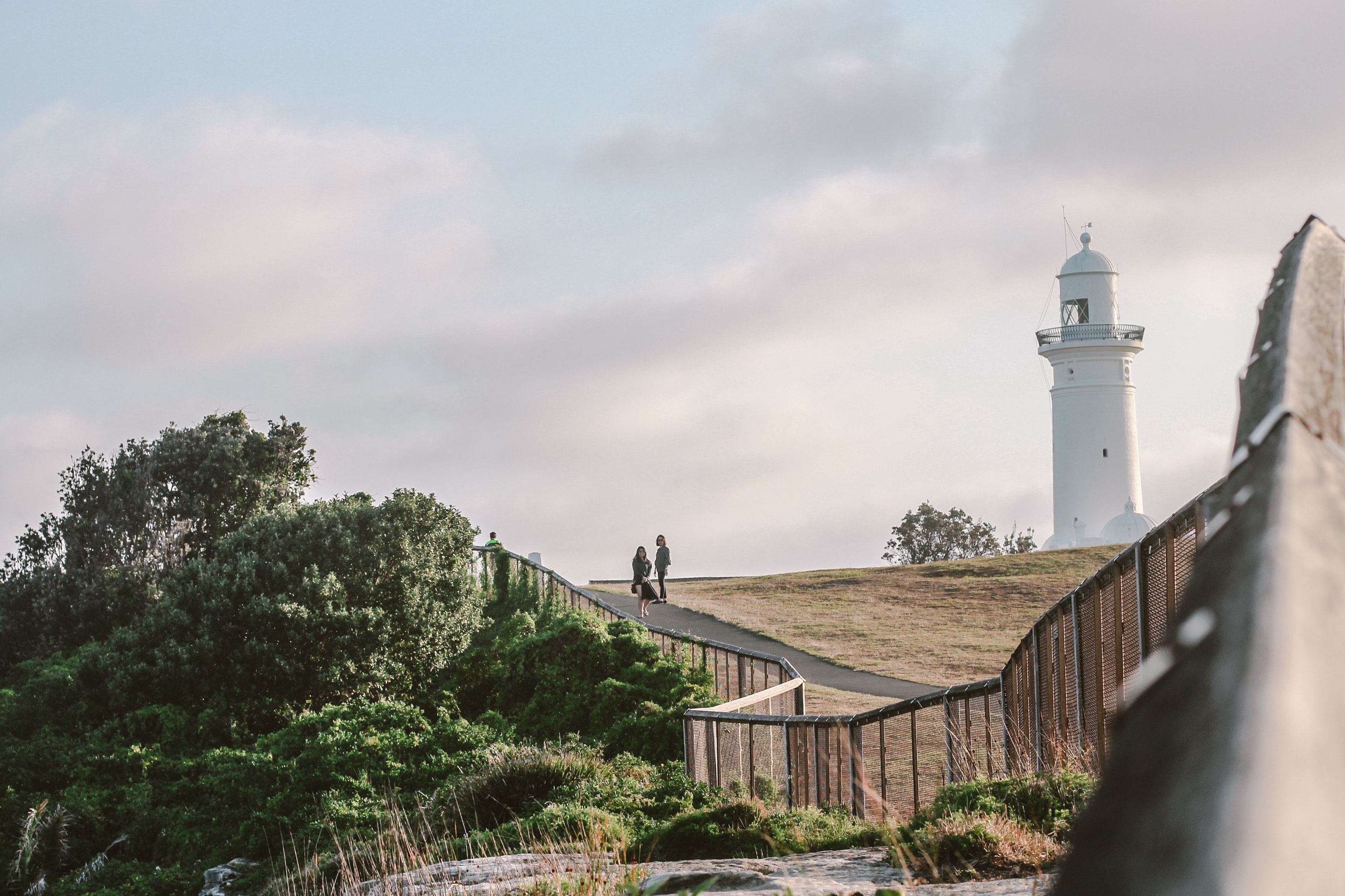 Two person standing near white lighthouse photo