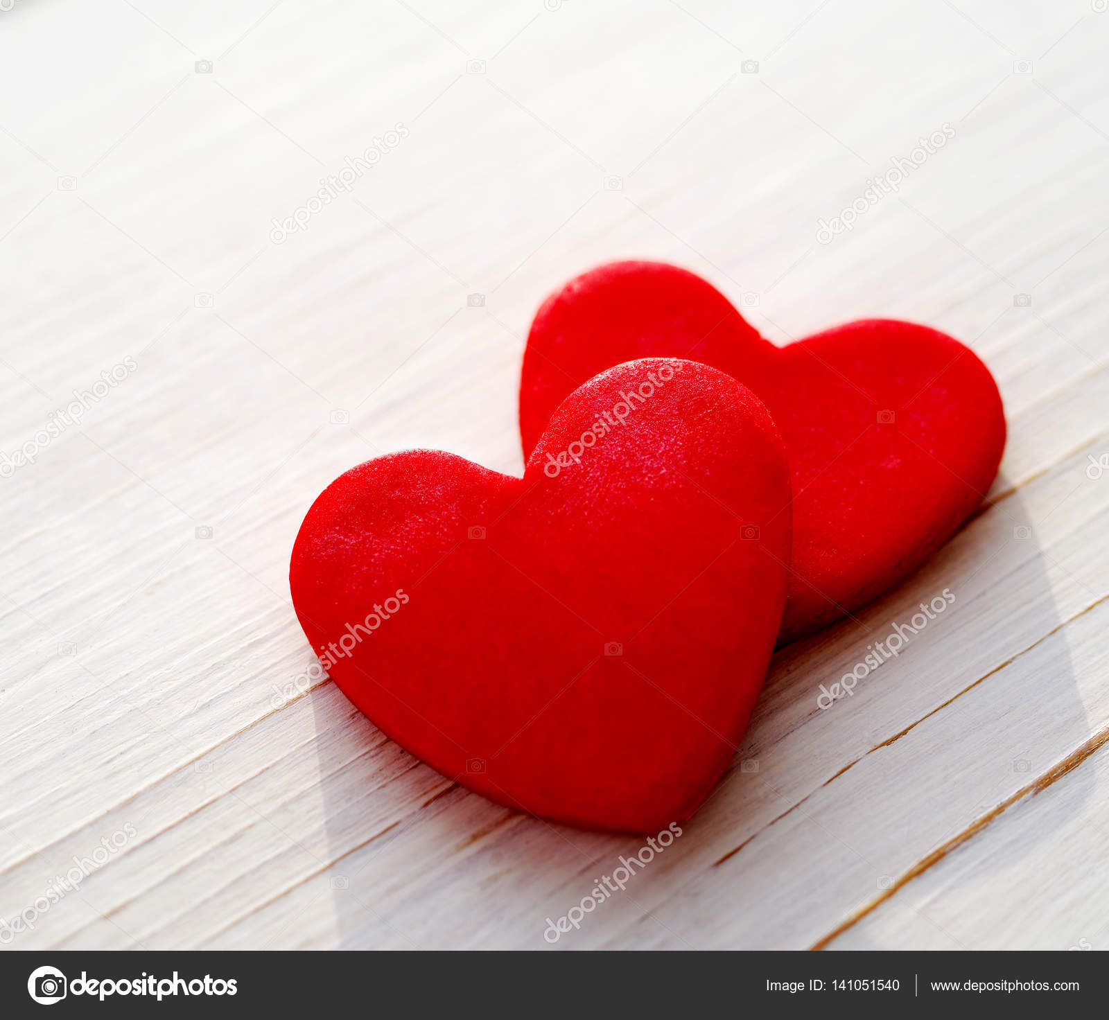 Two red hearts on a wooden white background, soft focus. Romantic ...