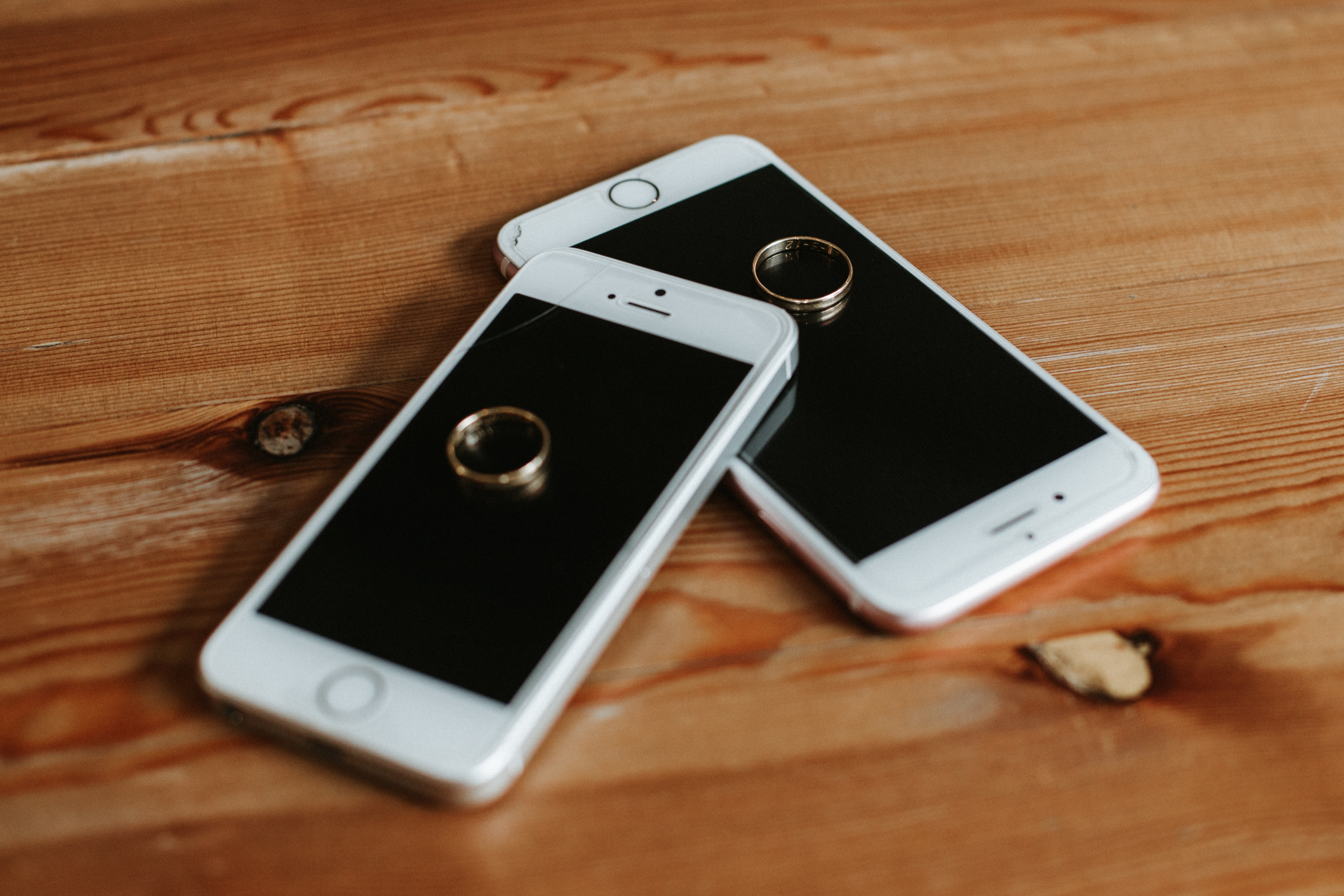 Two rose gold iphone 6s on brown wooden surface photo