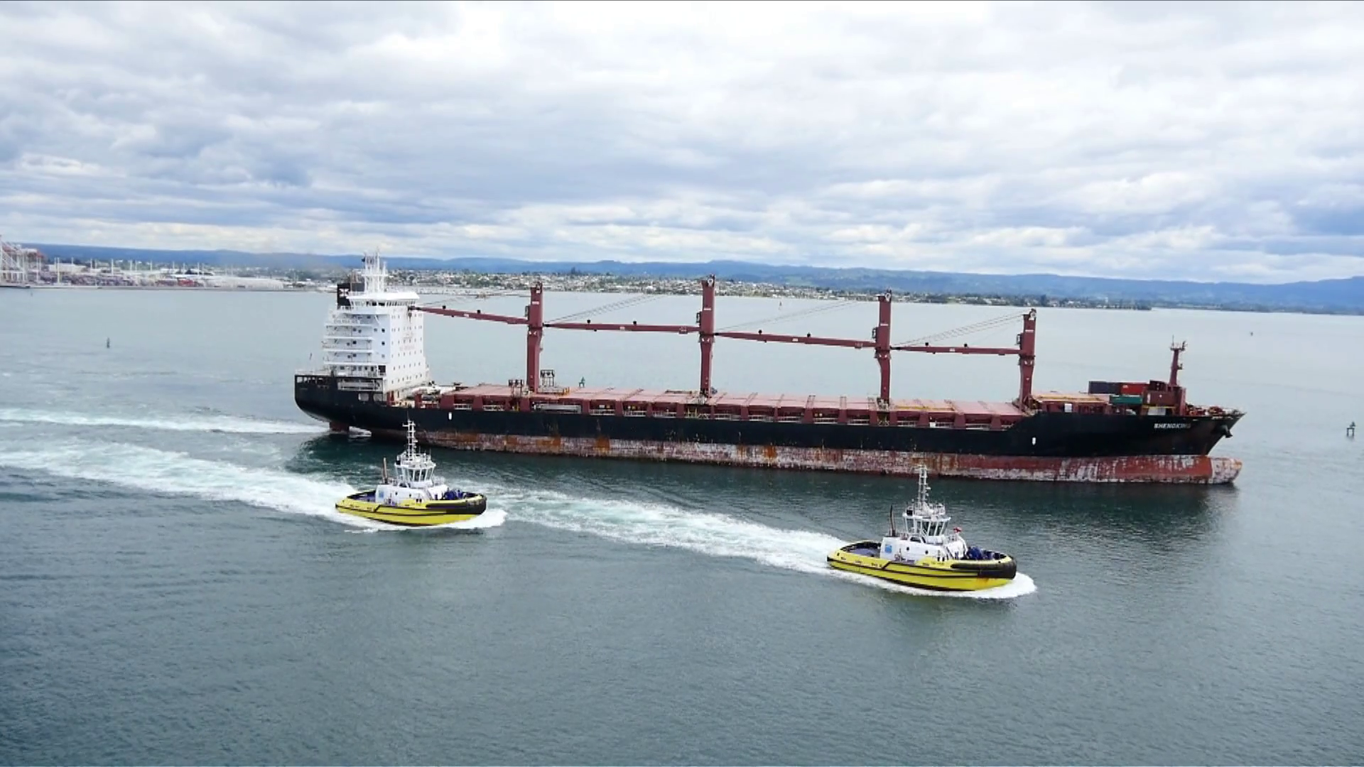 Two Tug Boats and a Cargo Ship Stock Video Footage - VideoBlocks
