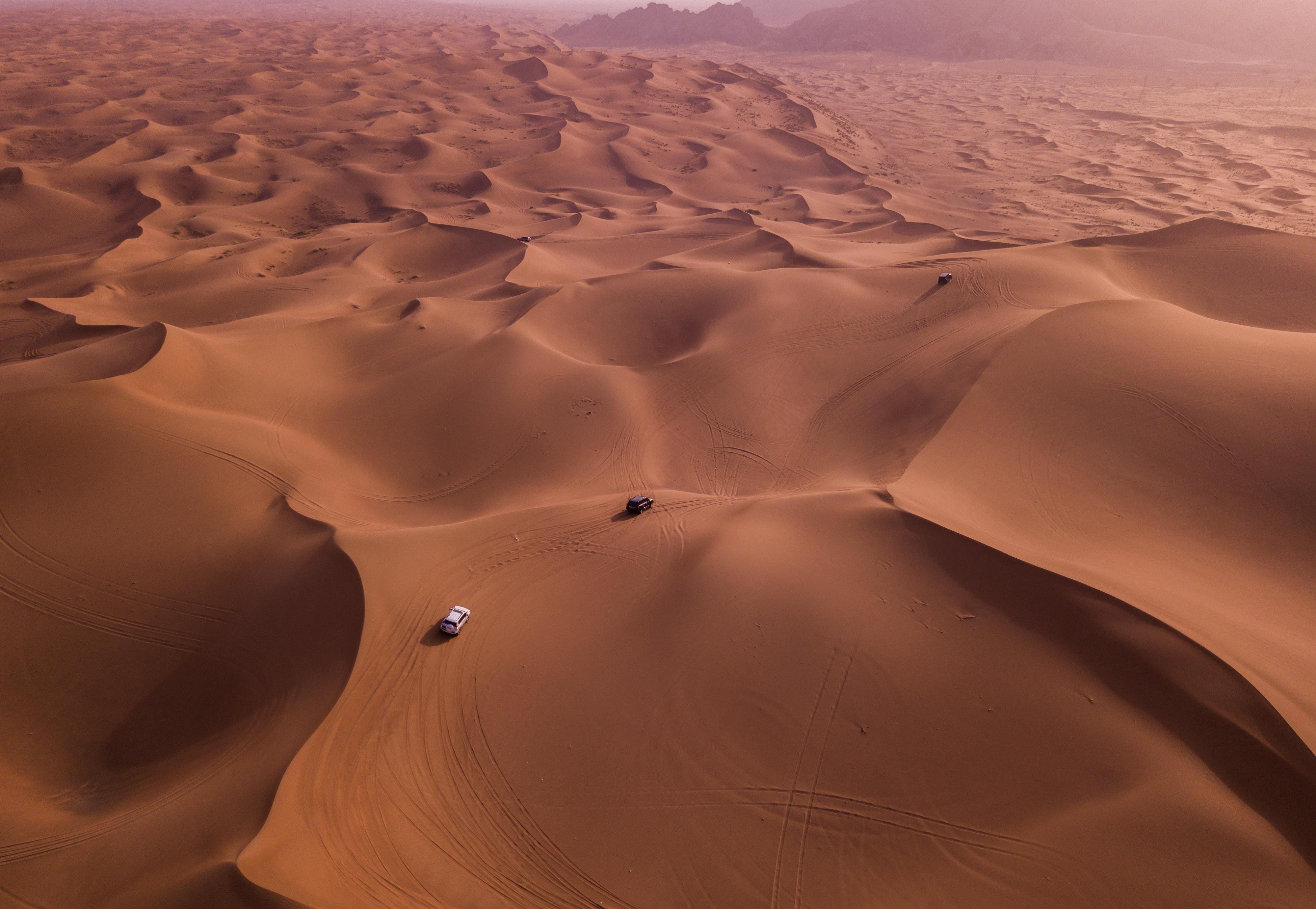 Two vehicles on desert dunes photo