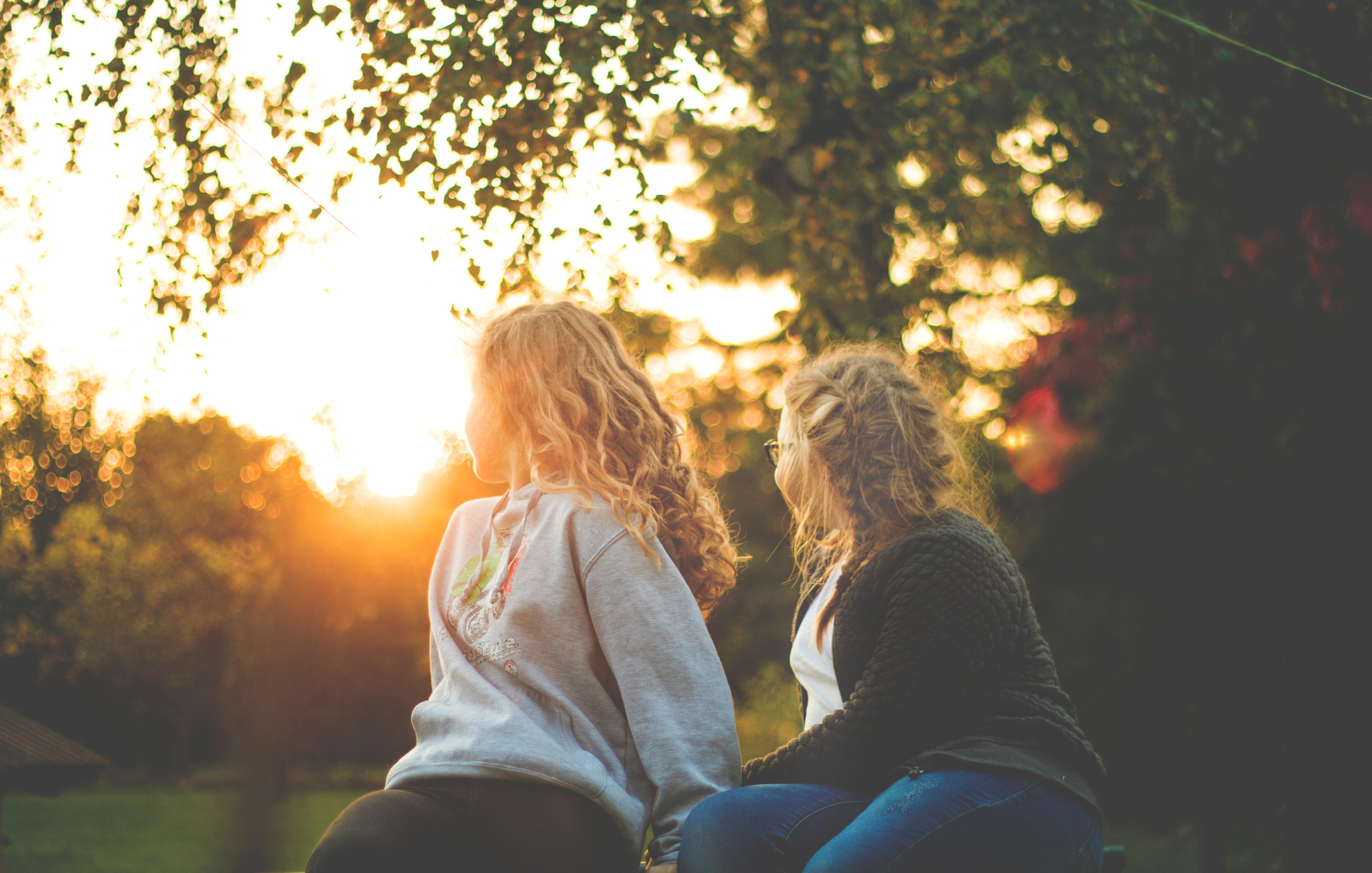 Two women sitting near green tree during sunset photo