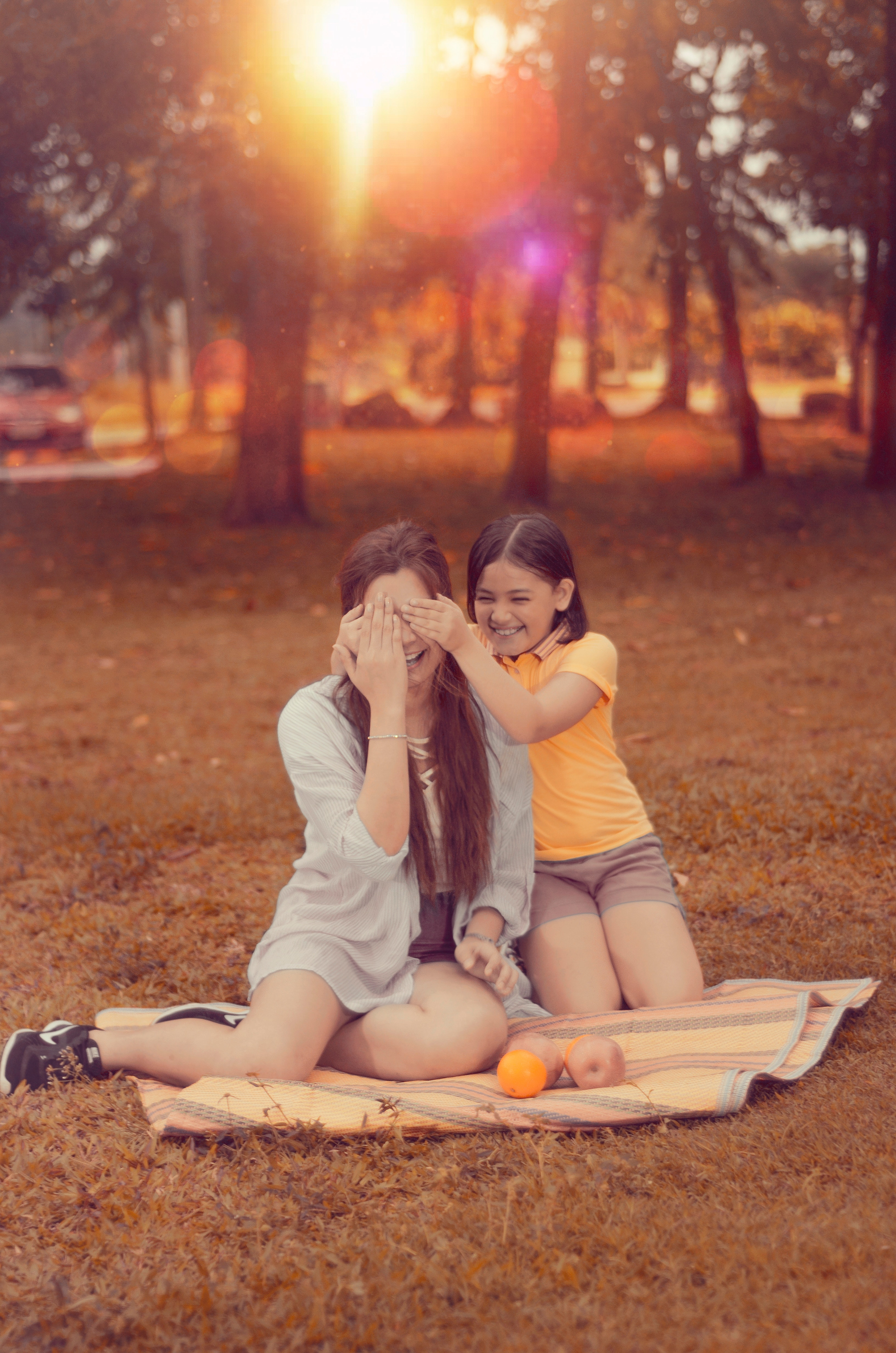 Two women sitting on brown picnic mat during sunset photo