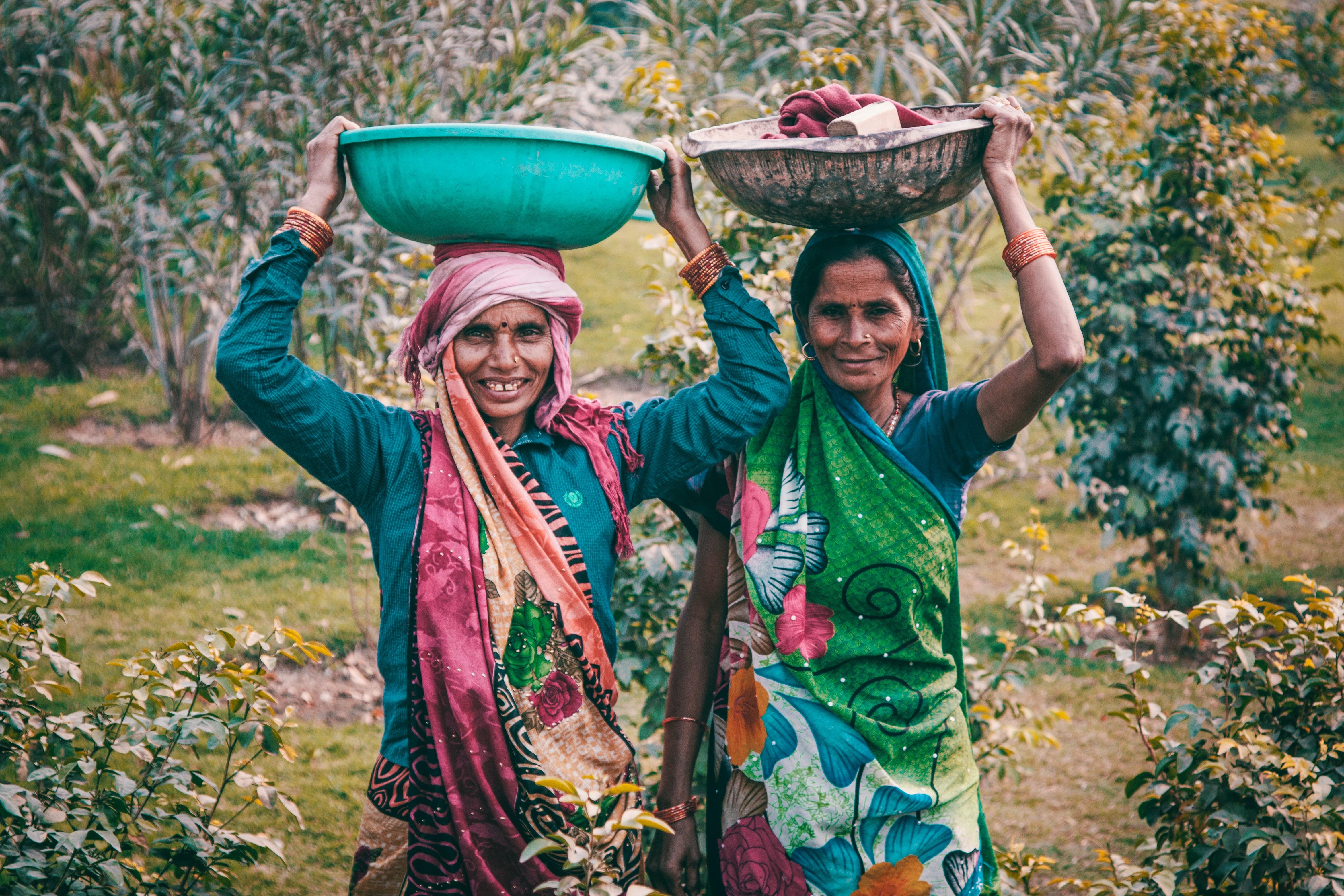 Two women wearing traditional dress carrying basins photo