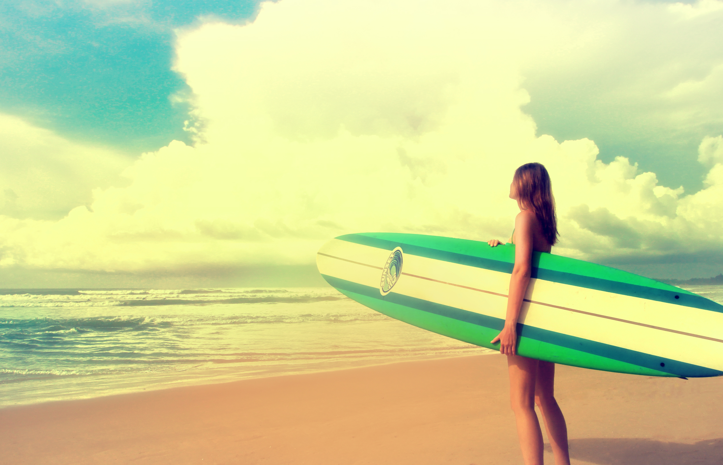 Up to the challenge - woman with surfboard ready to surf photo