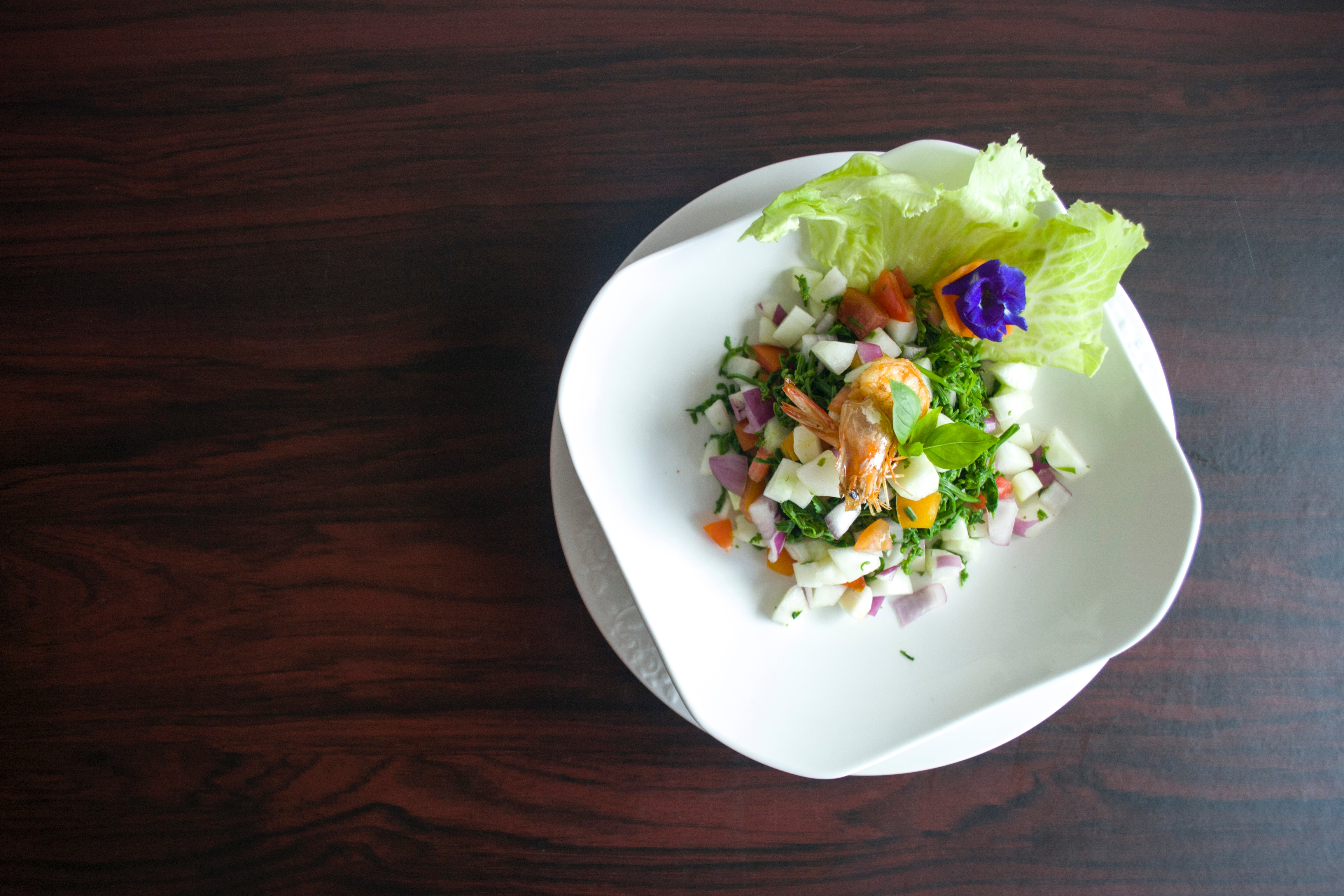 Vegetable salad with shrimp on white plate photo