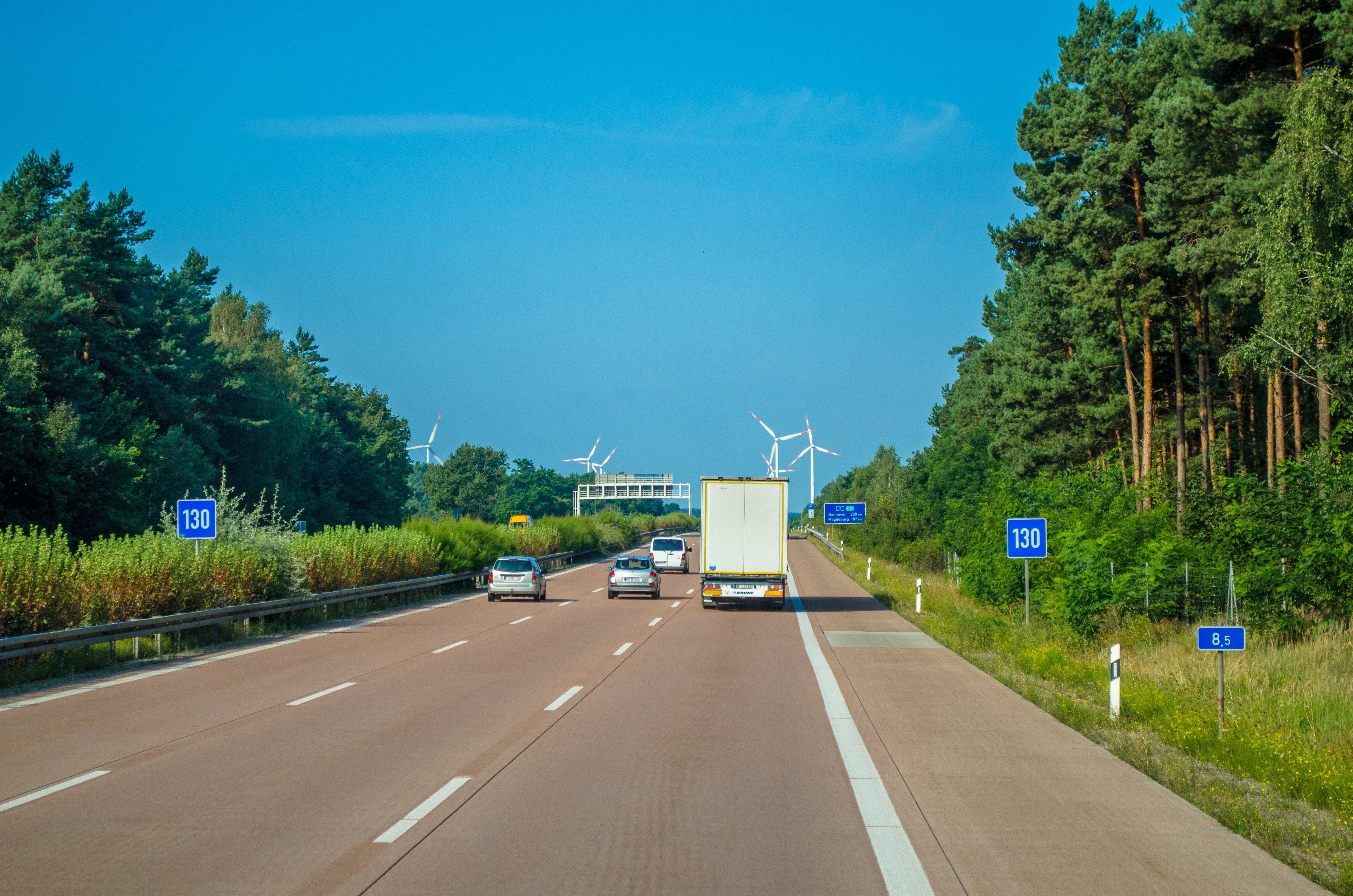 Vehicle driving on freeway towards wind turbines photo