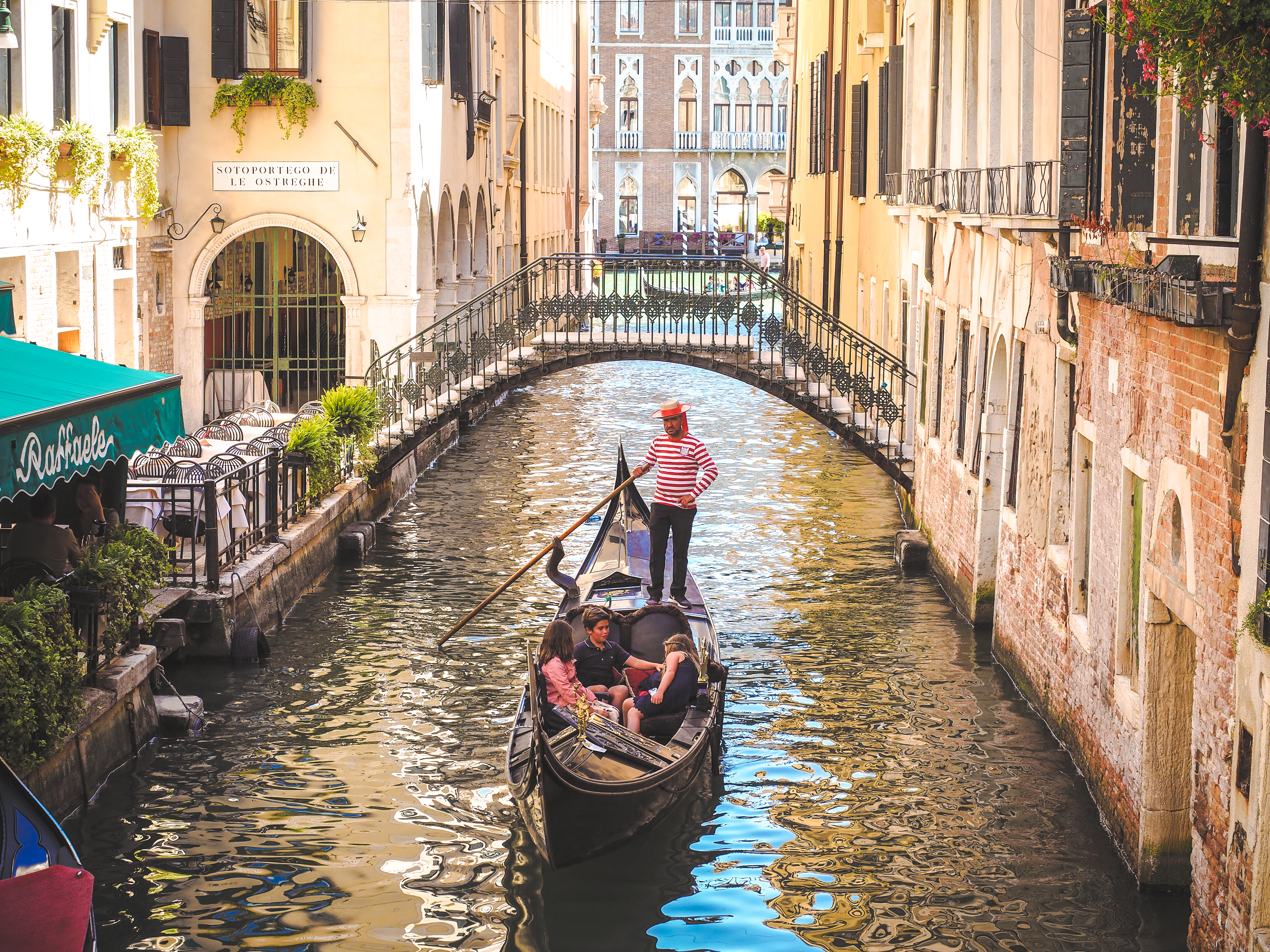 Traditional Gondola with tourists in Venice canal
