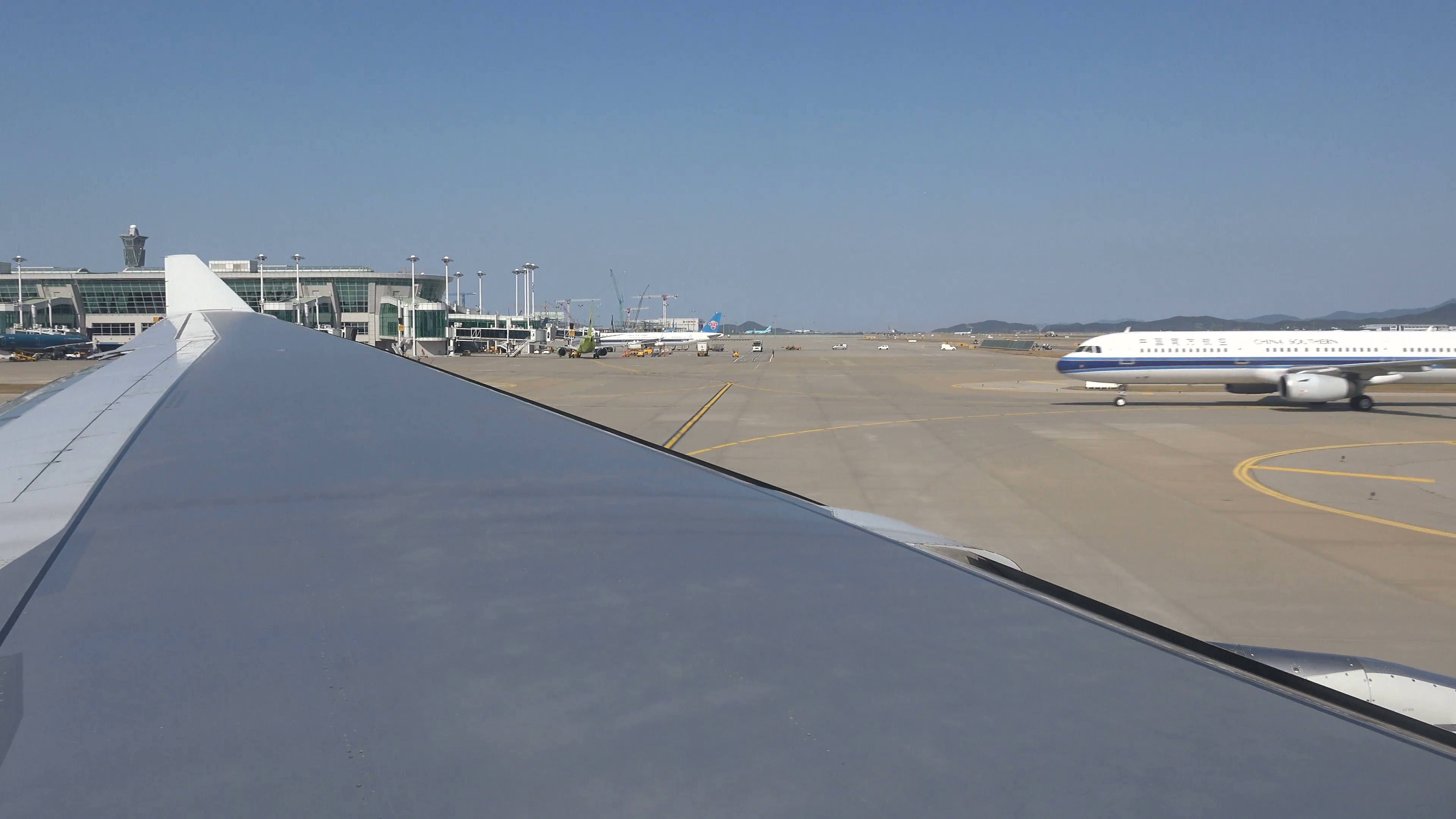 A Korean Air flight taxiing to the runway, view of the wing tip, at ...