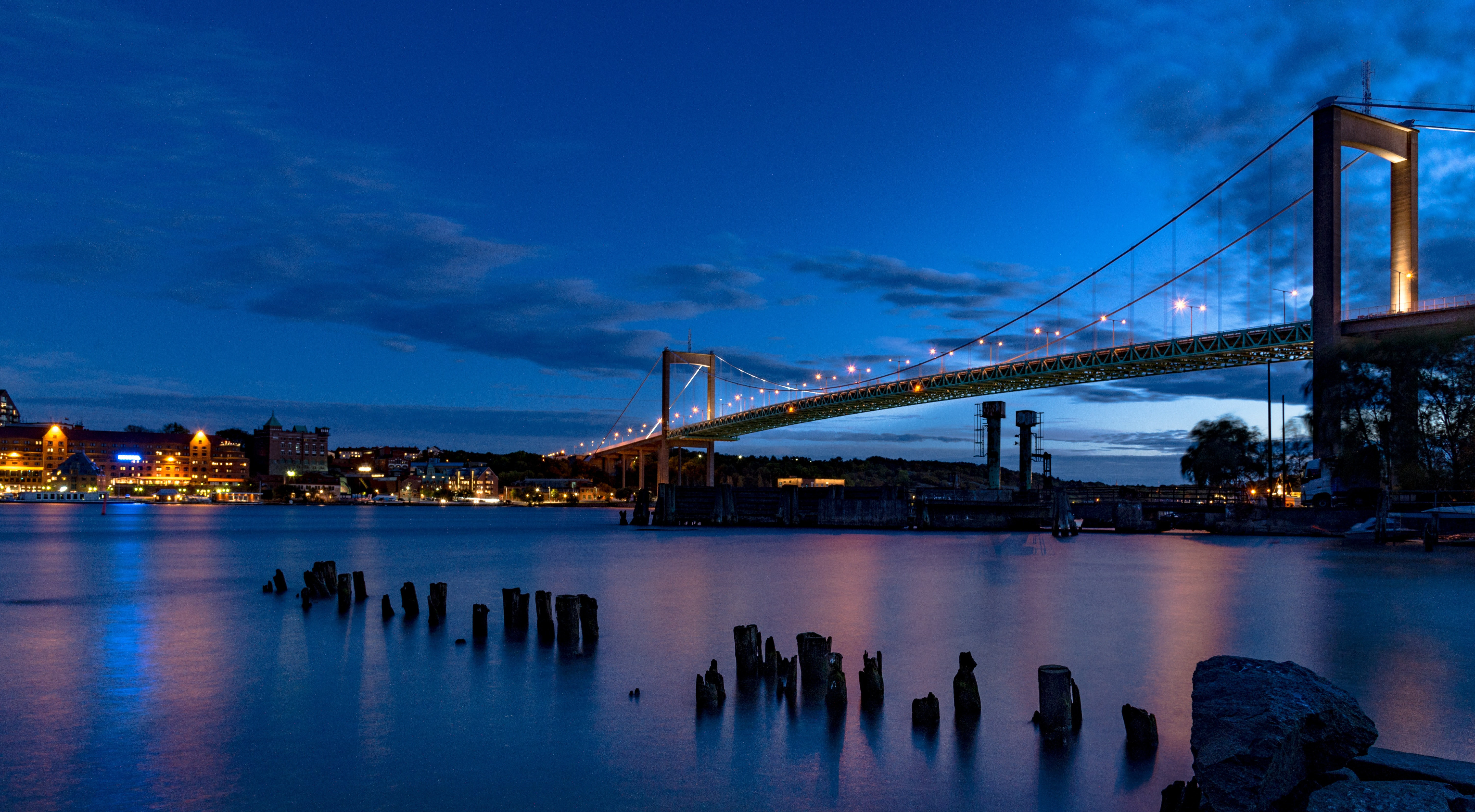 View of body of water below city suspension bridge photo