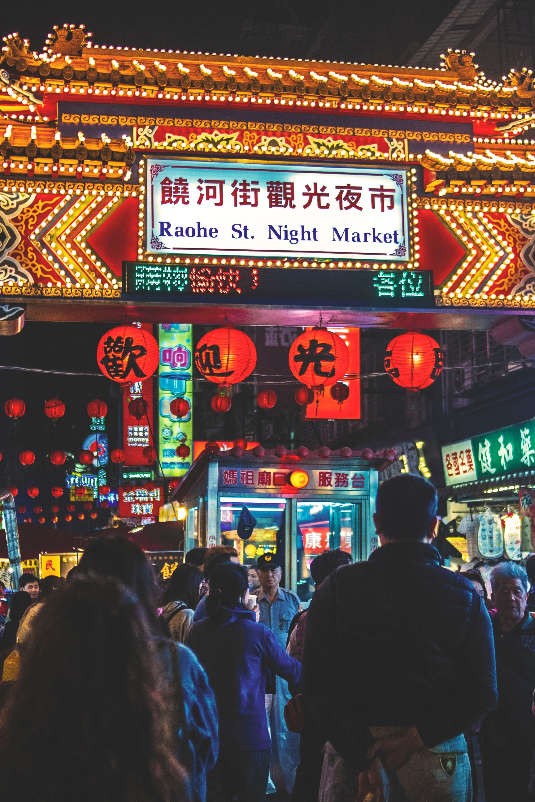 View of raohe st. night market arch with kanji texts and group of people photo