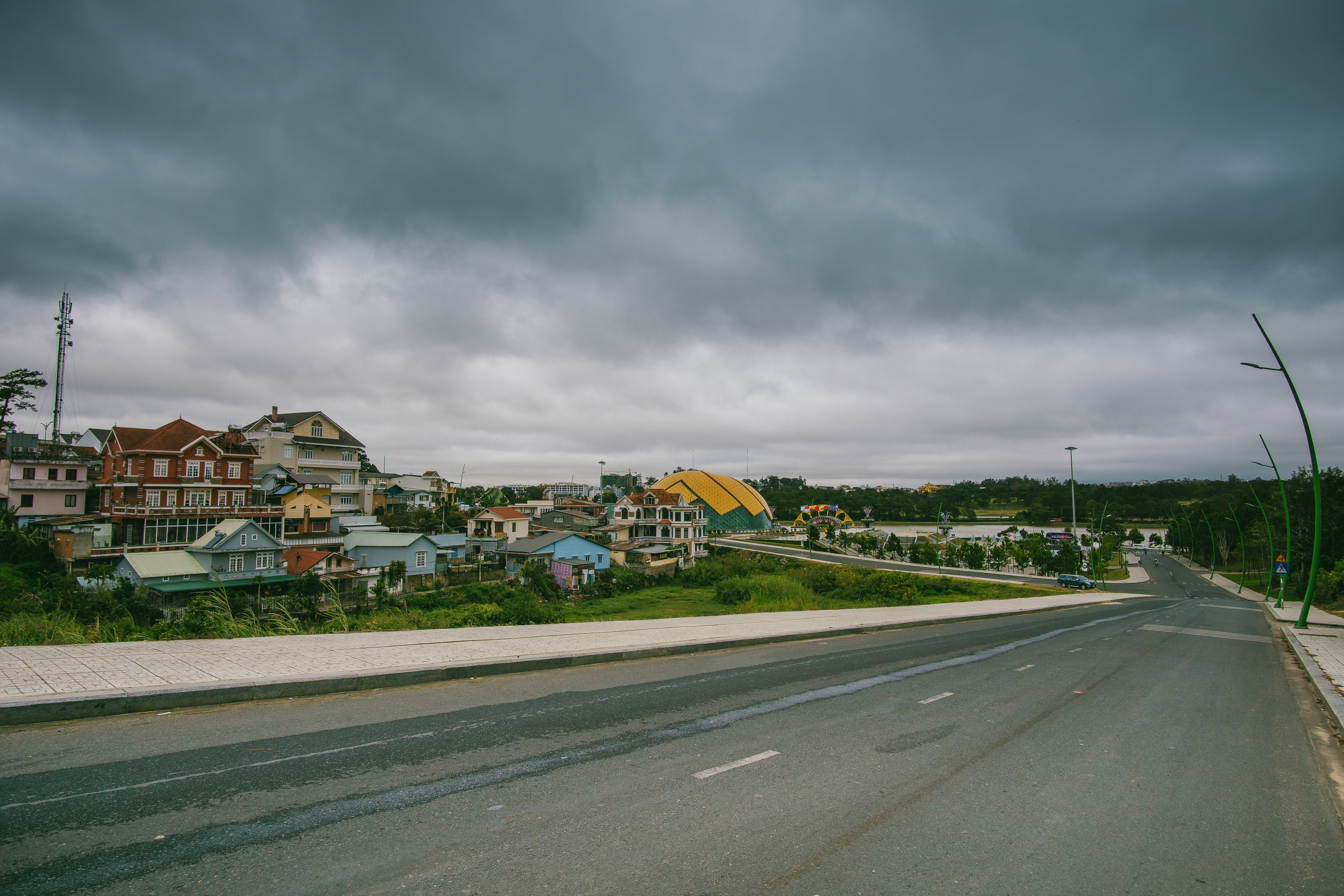 Village beside road under cloudy sky photo