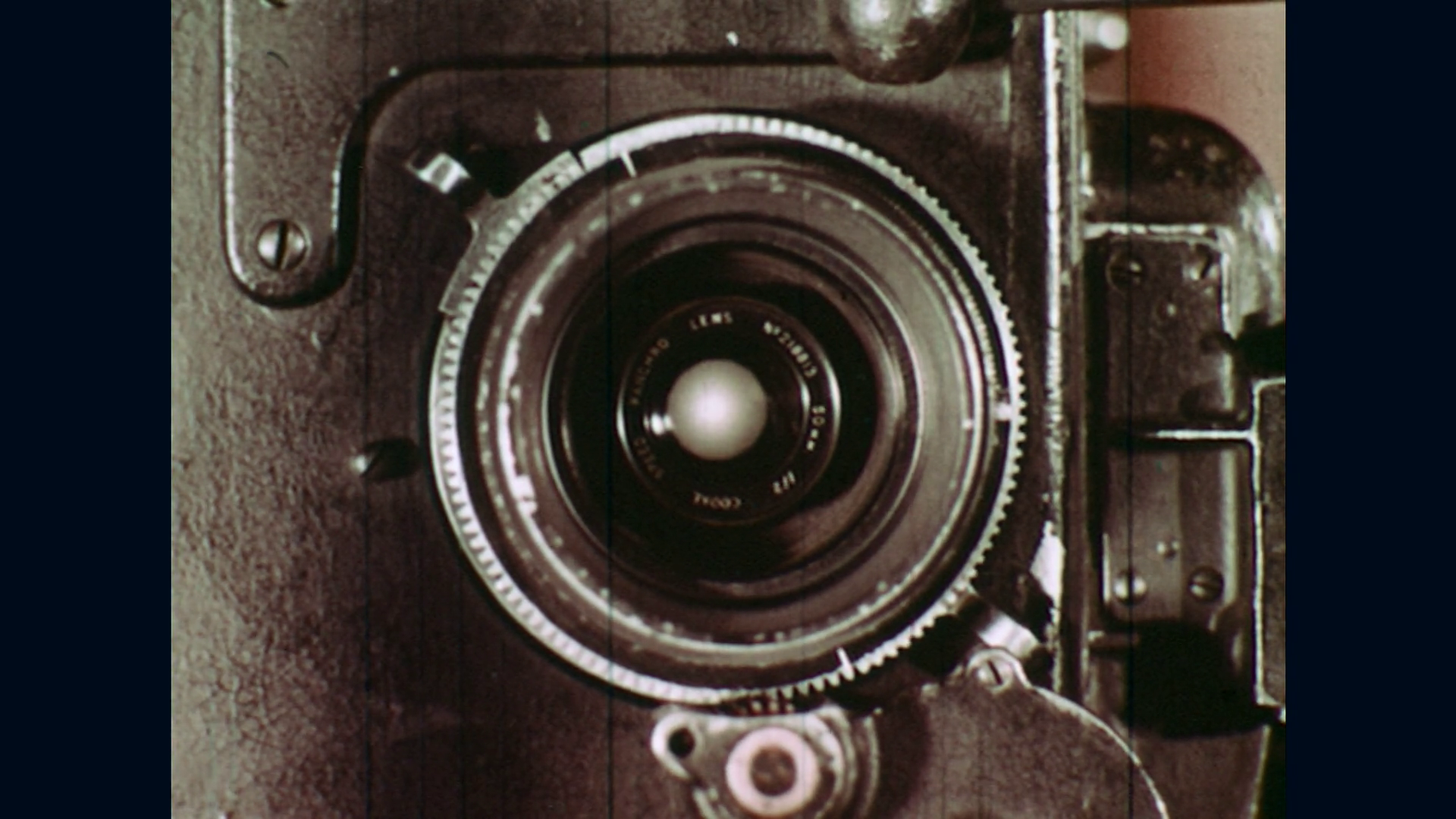 UNITED STATES: 1940s: Close up of vintage camera lens. Two men turn ...