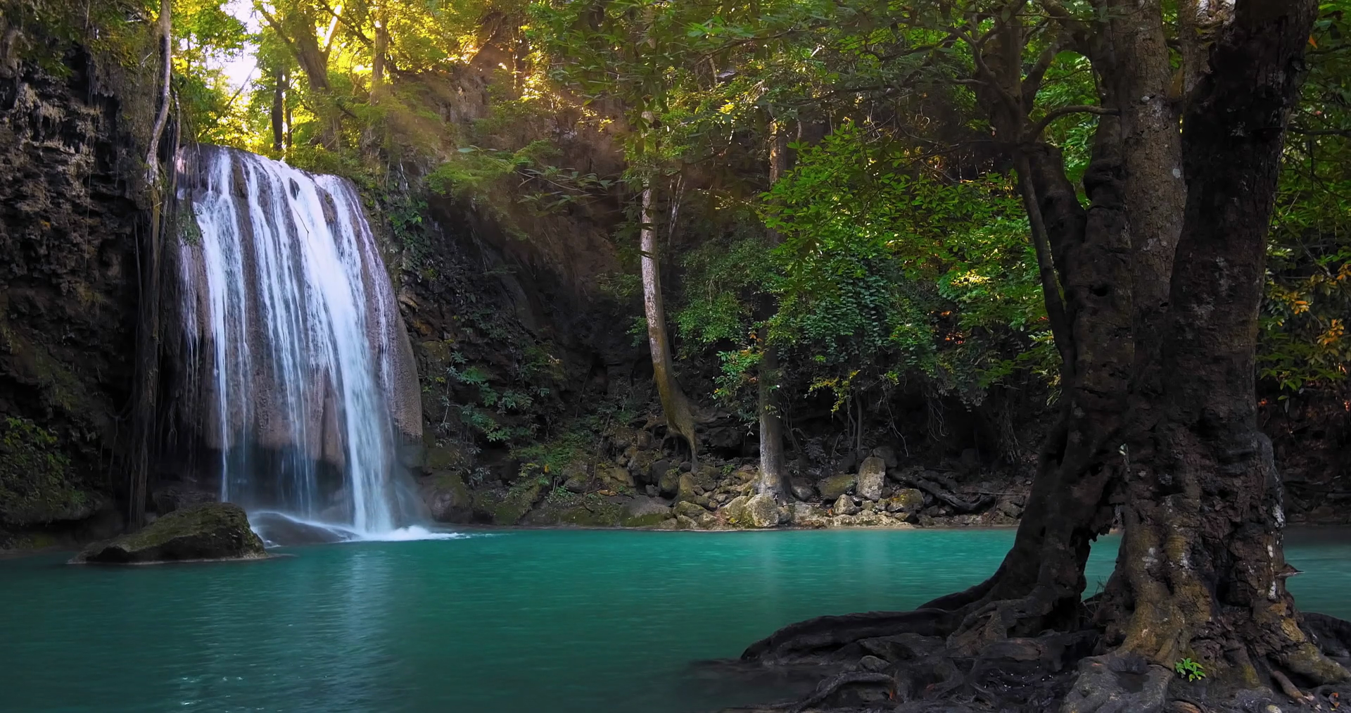 Clear waterfall flowing down turquoise clean river surrounded by ...