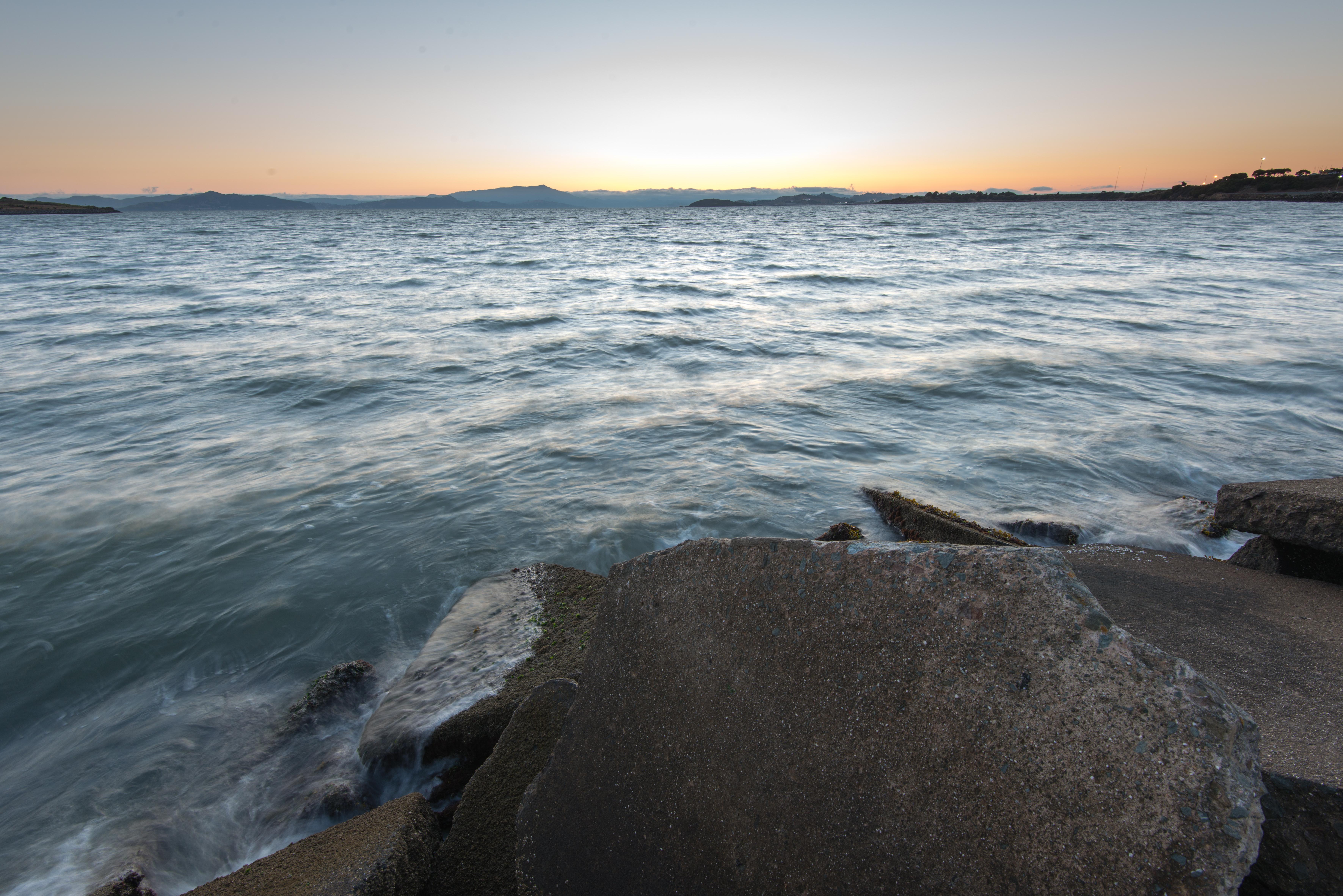 Waves crashing on rocks at bay shore at sunset photo