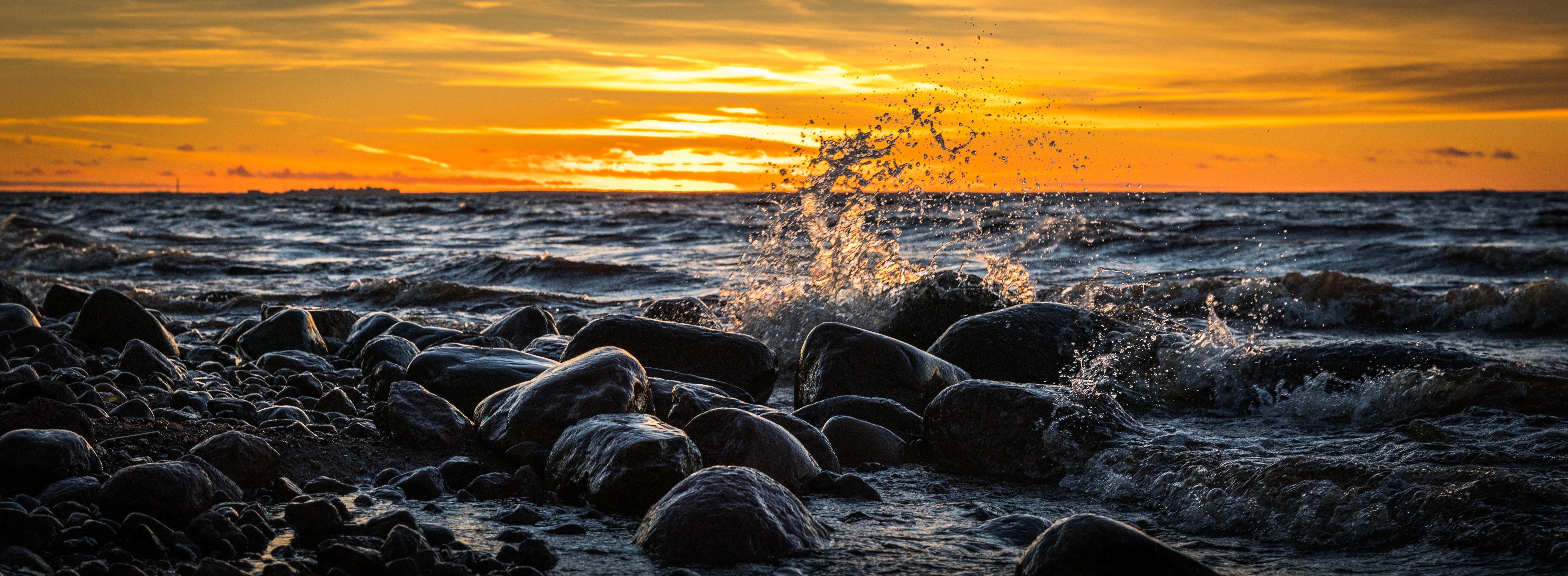 Waves splashing at stones on beach during sunset photo