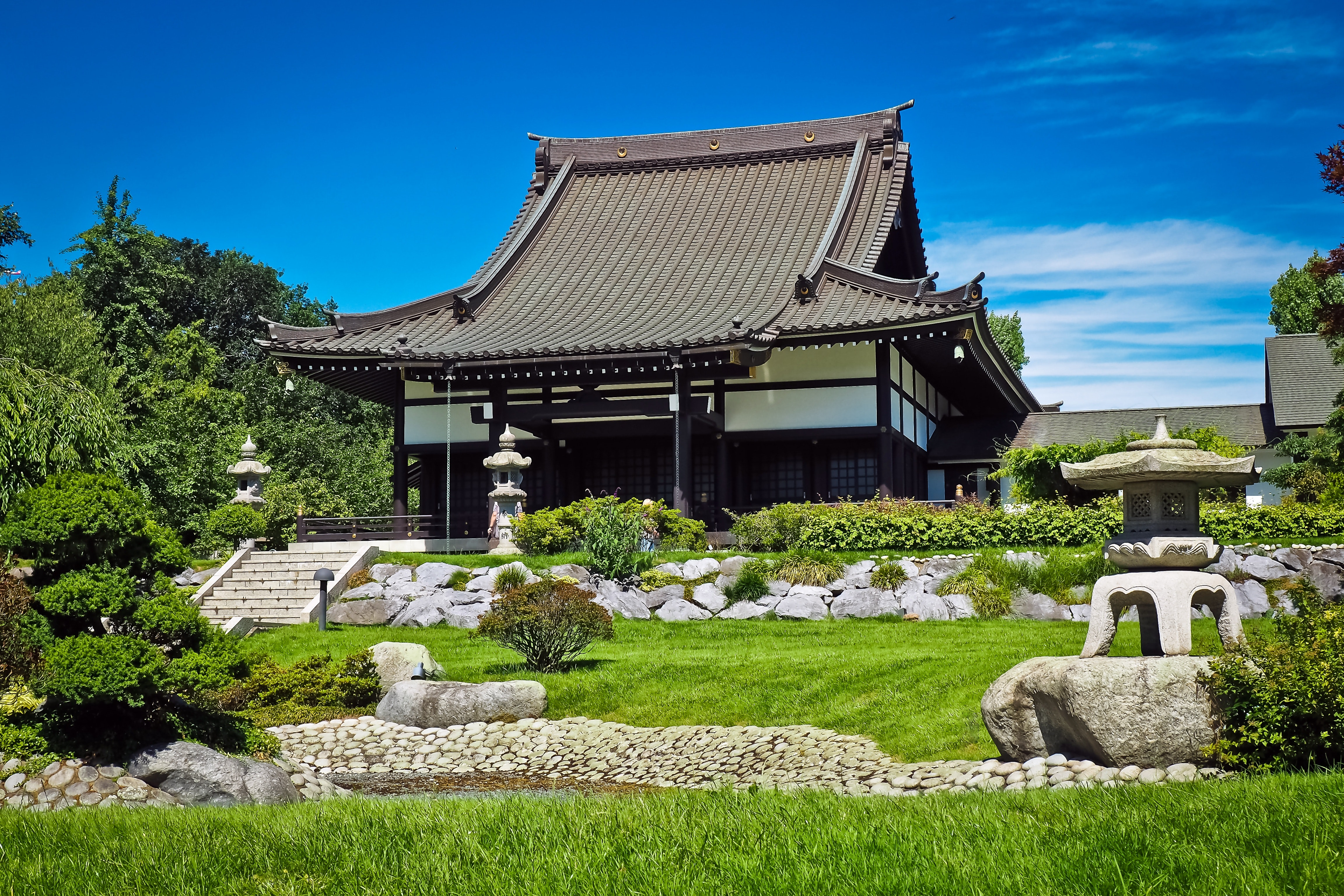 White and black temple surrounded by green grass field during daytime photo