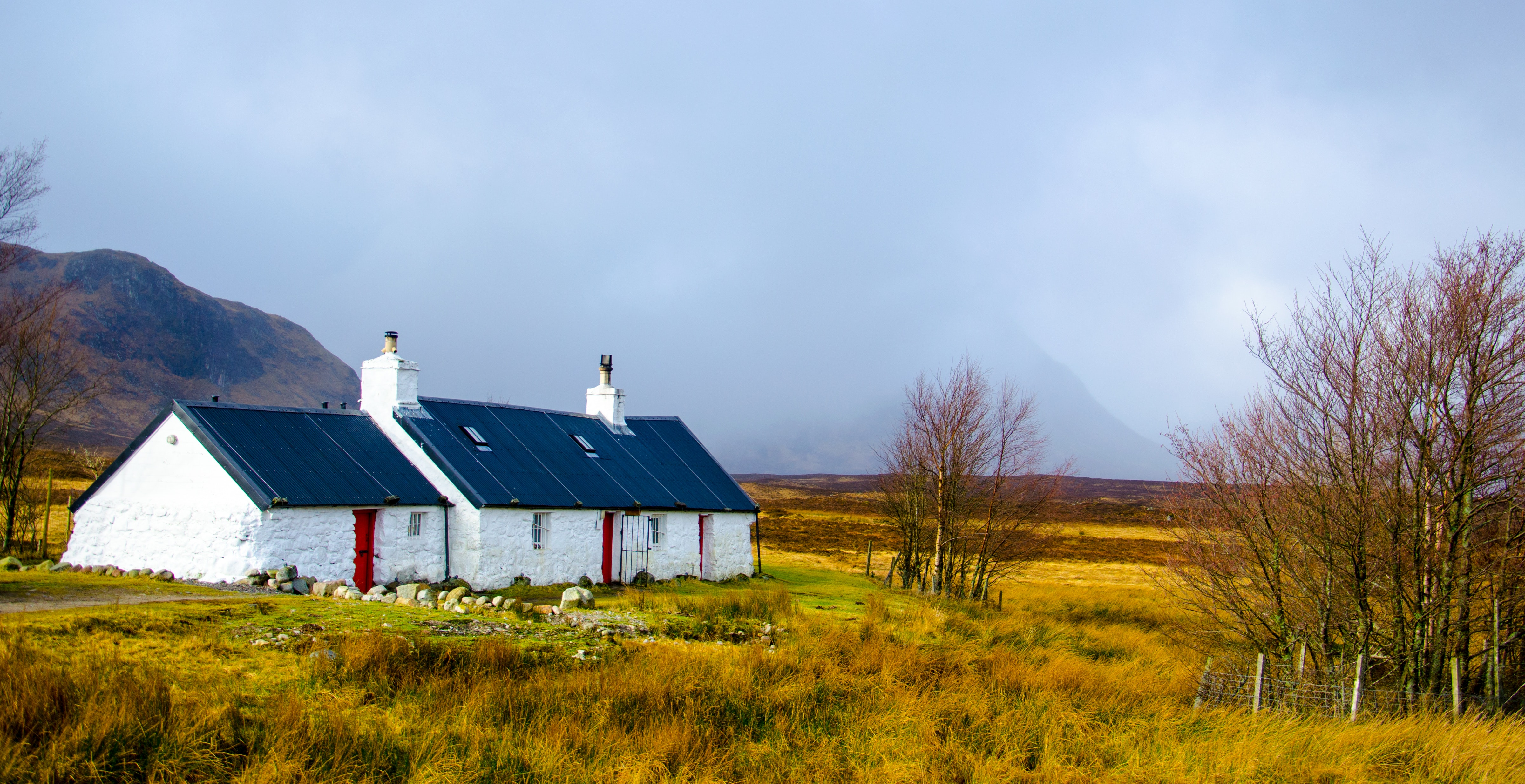 White and blue house under cumulus nimbus clouds photo