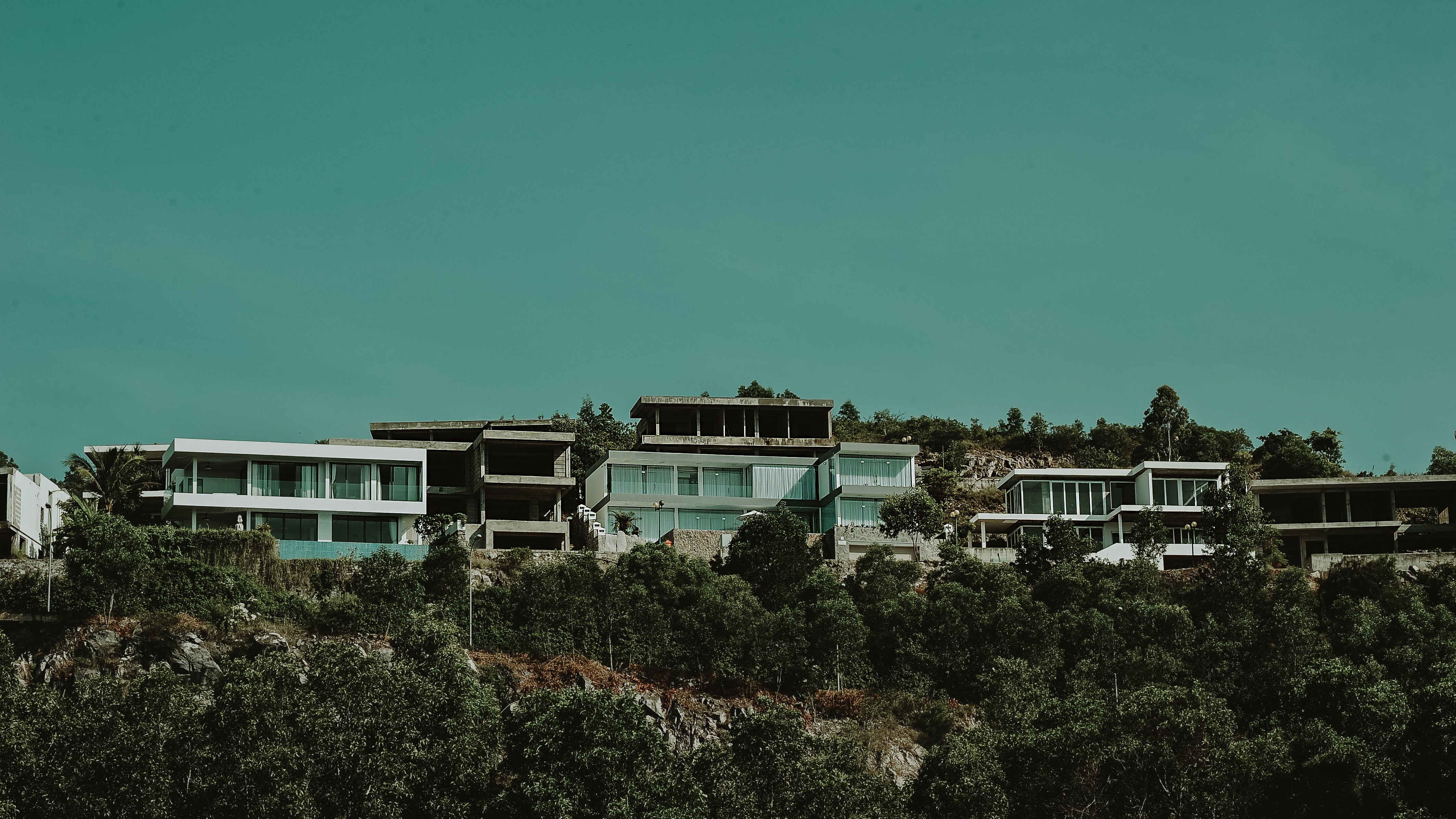 White And Gray Concrete Buildings With Green Trees Under Sky Outdoors Mountain