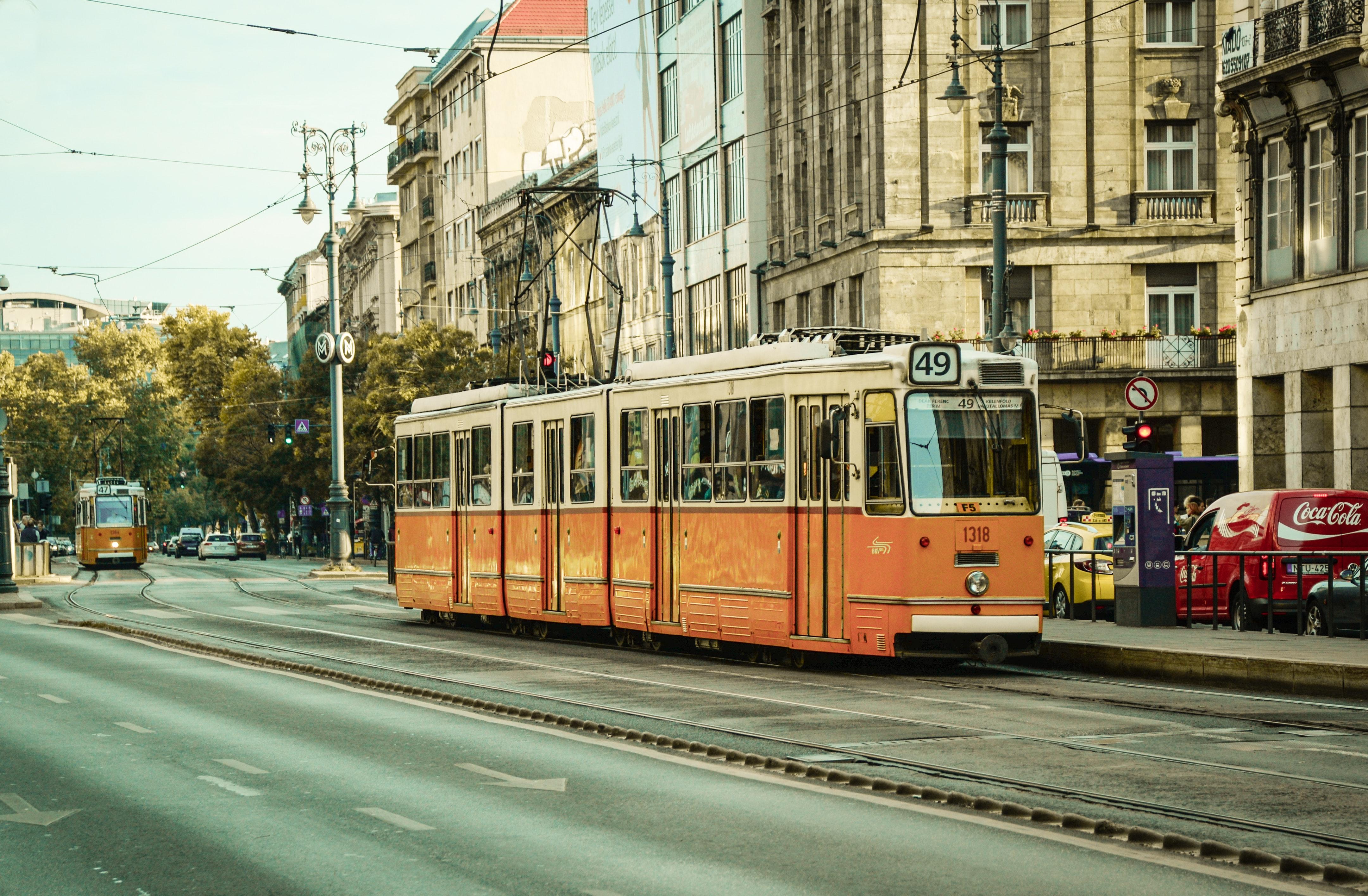 White and orange train near city buildings photo