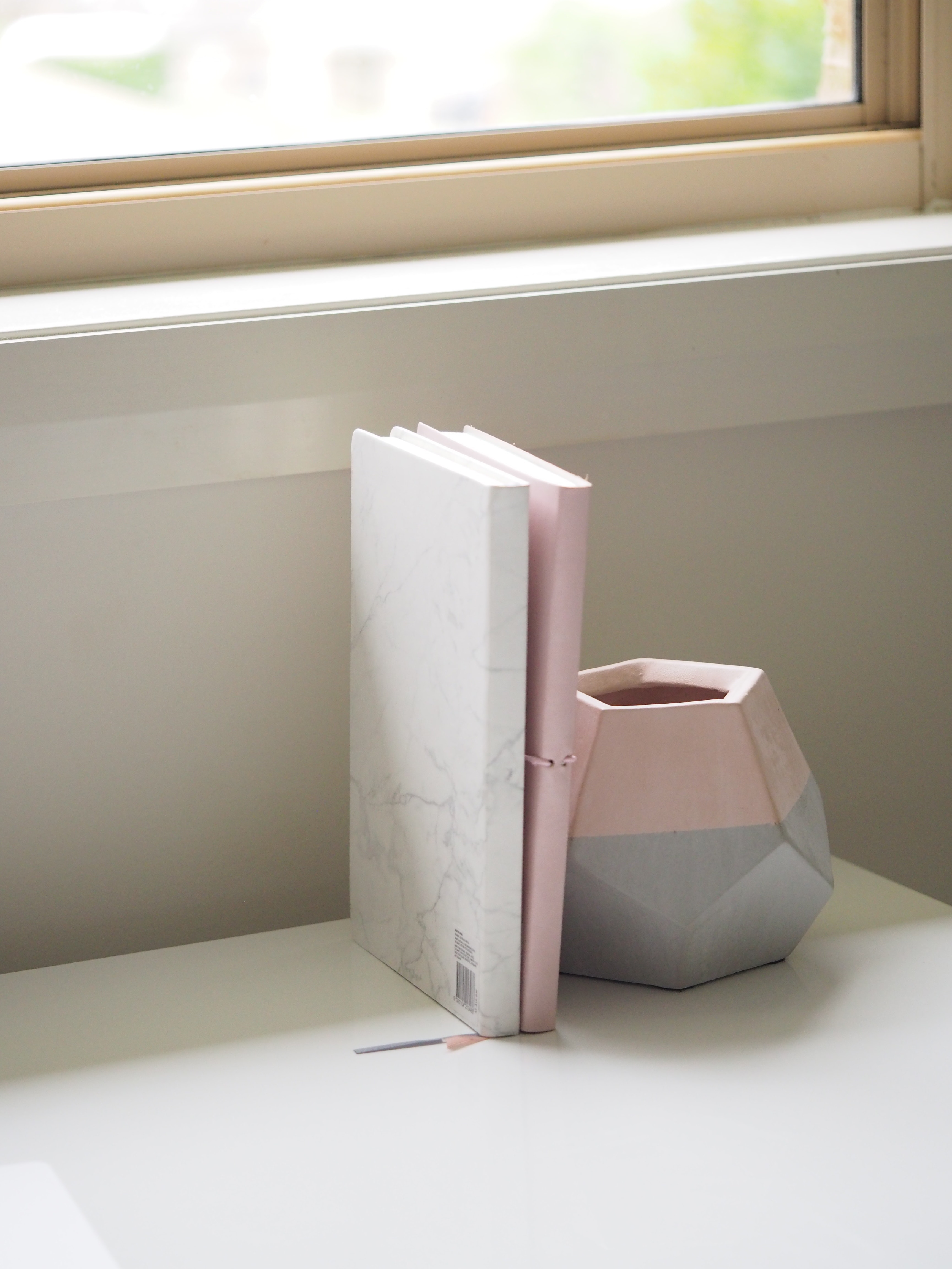 White and pink books piled beside pink and gray ceramic vase photo