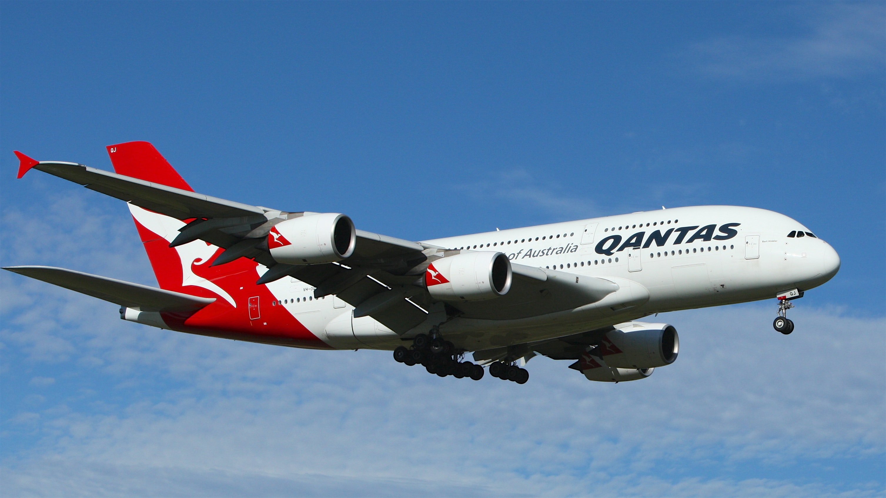 White and red qantas airplane fly high under blue and white clouds photo