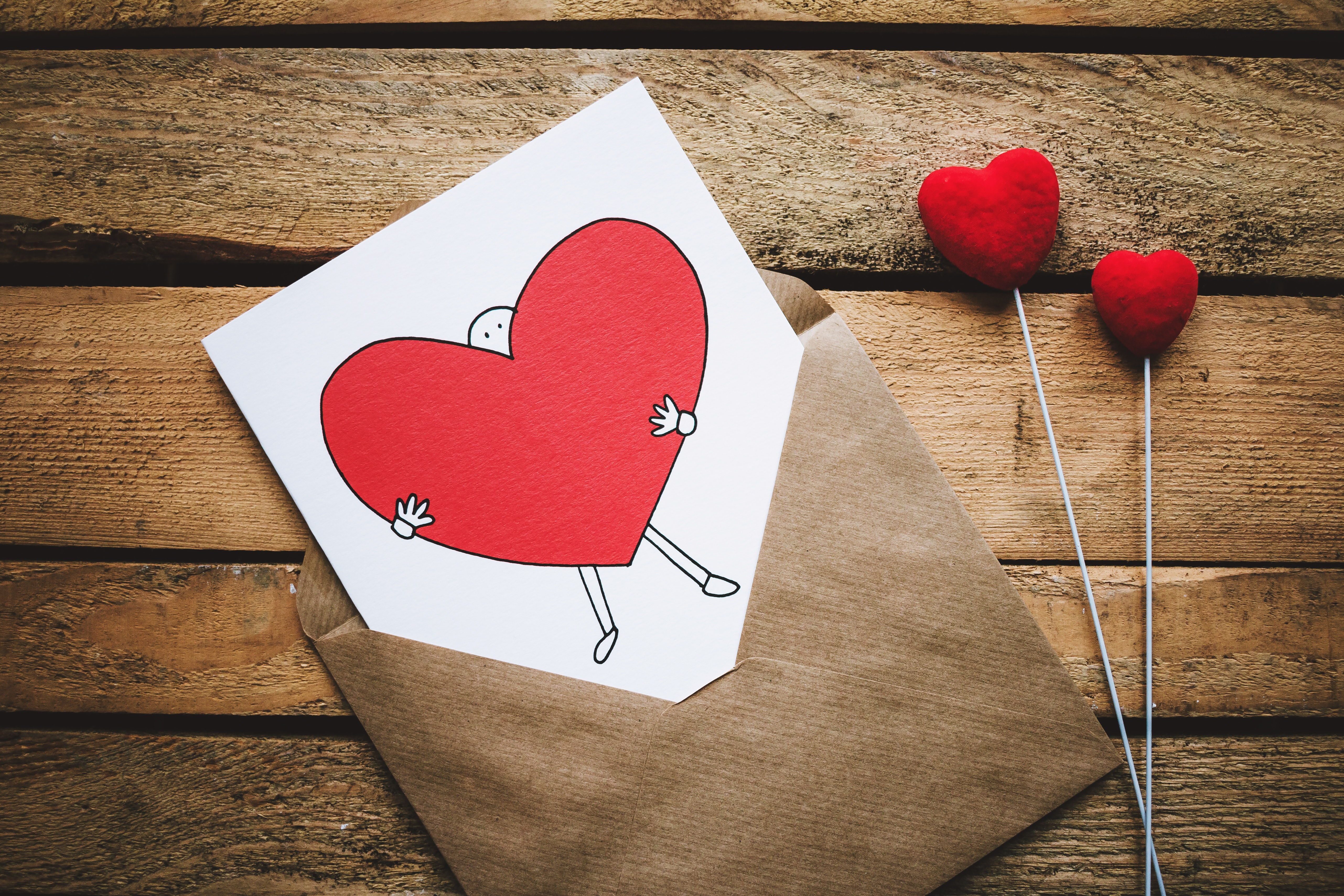 White, Black, and Red Person Carrying Heart Illustration in Brown Envelope, Paper, Wood, Valentines day, Table, HQ Photo
