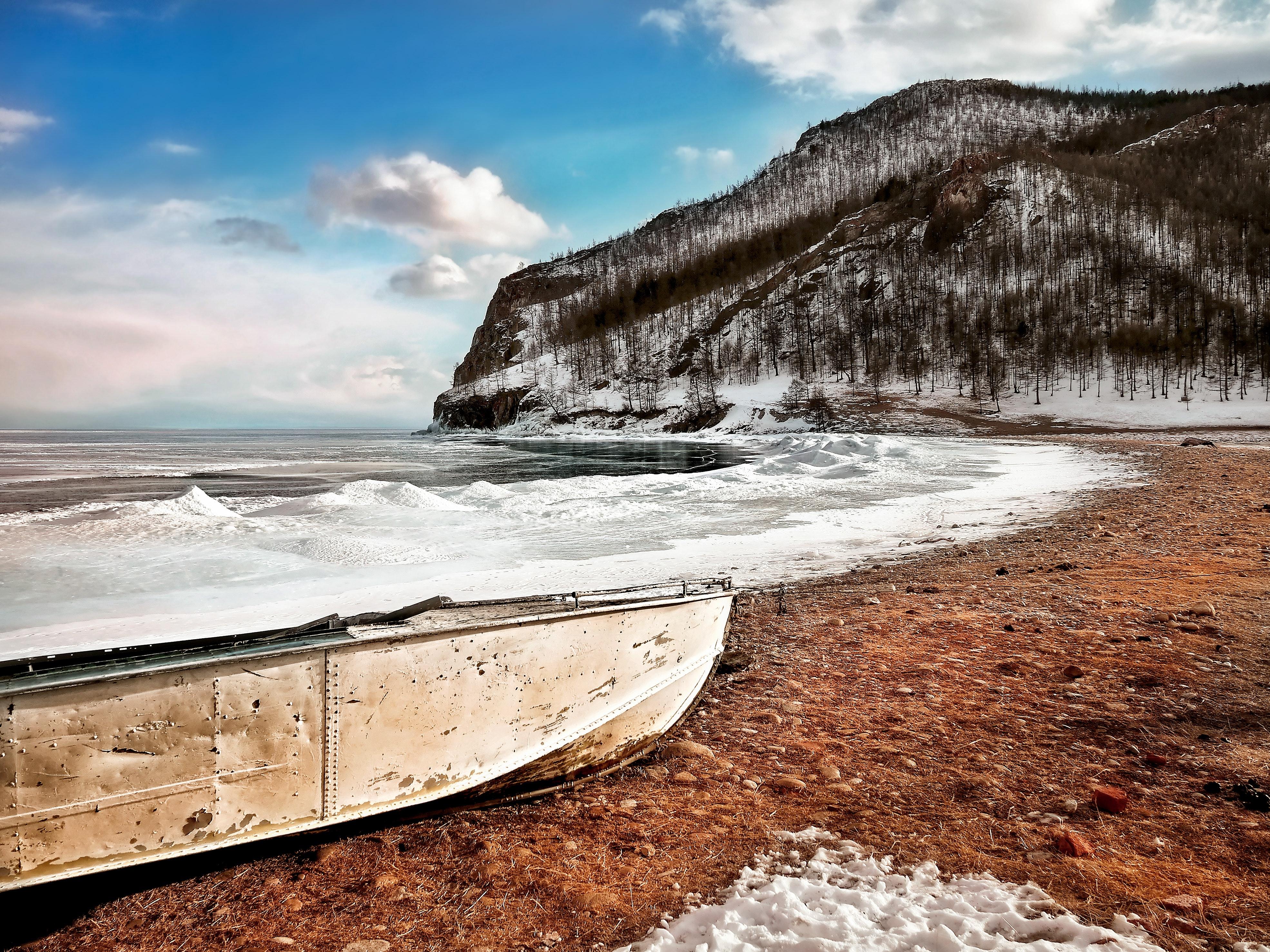 White boat on seashore near mountain under white and blue sky photo