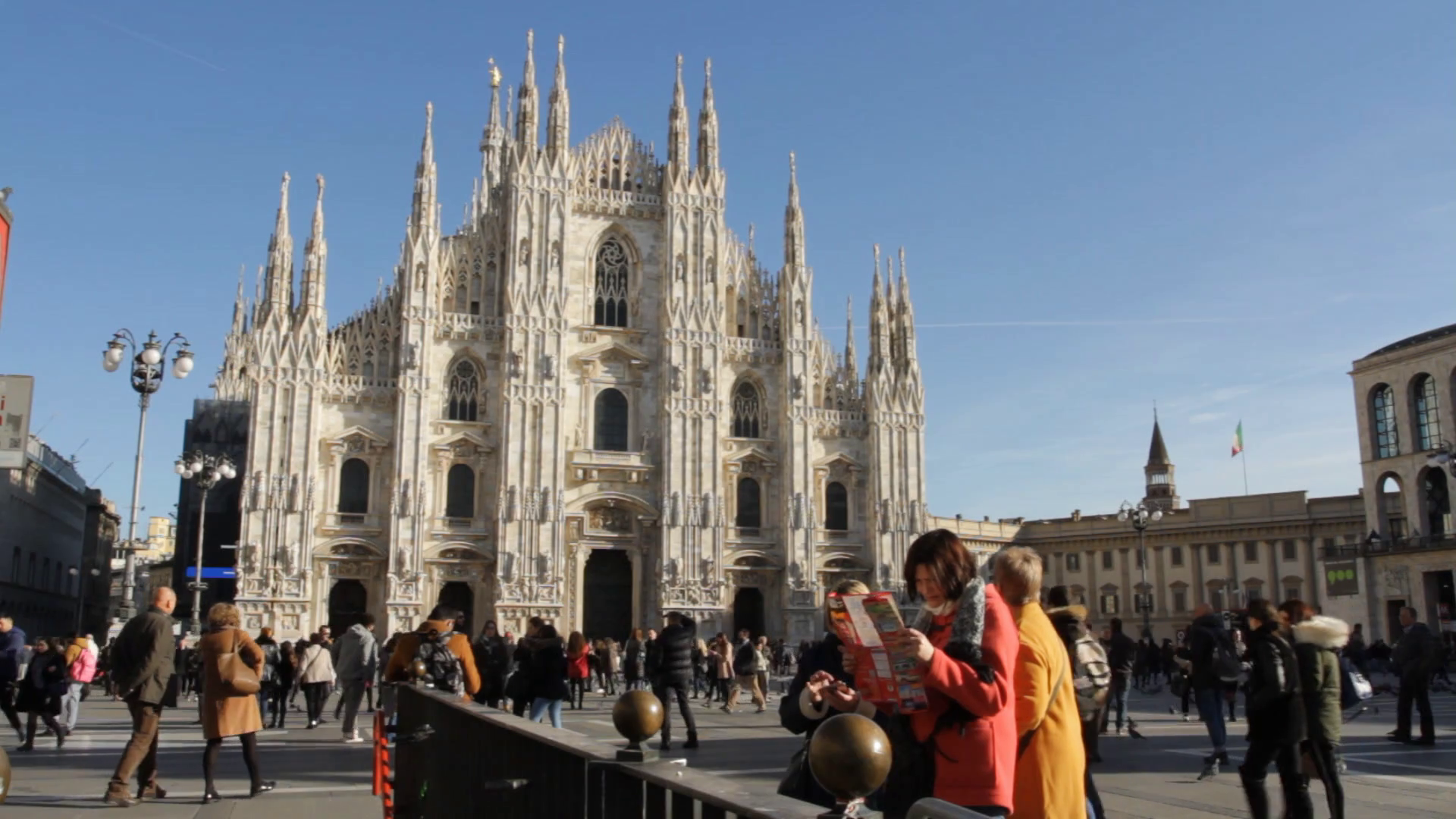 Milan, Gothic cathedral pearly white facade with tourist reading a ...