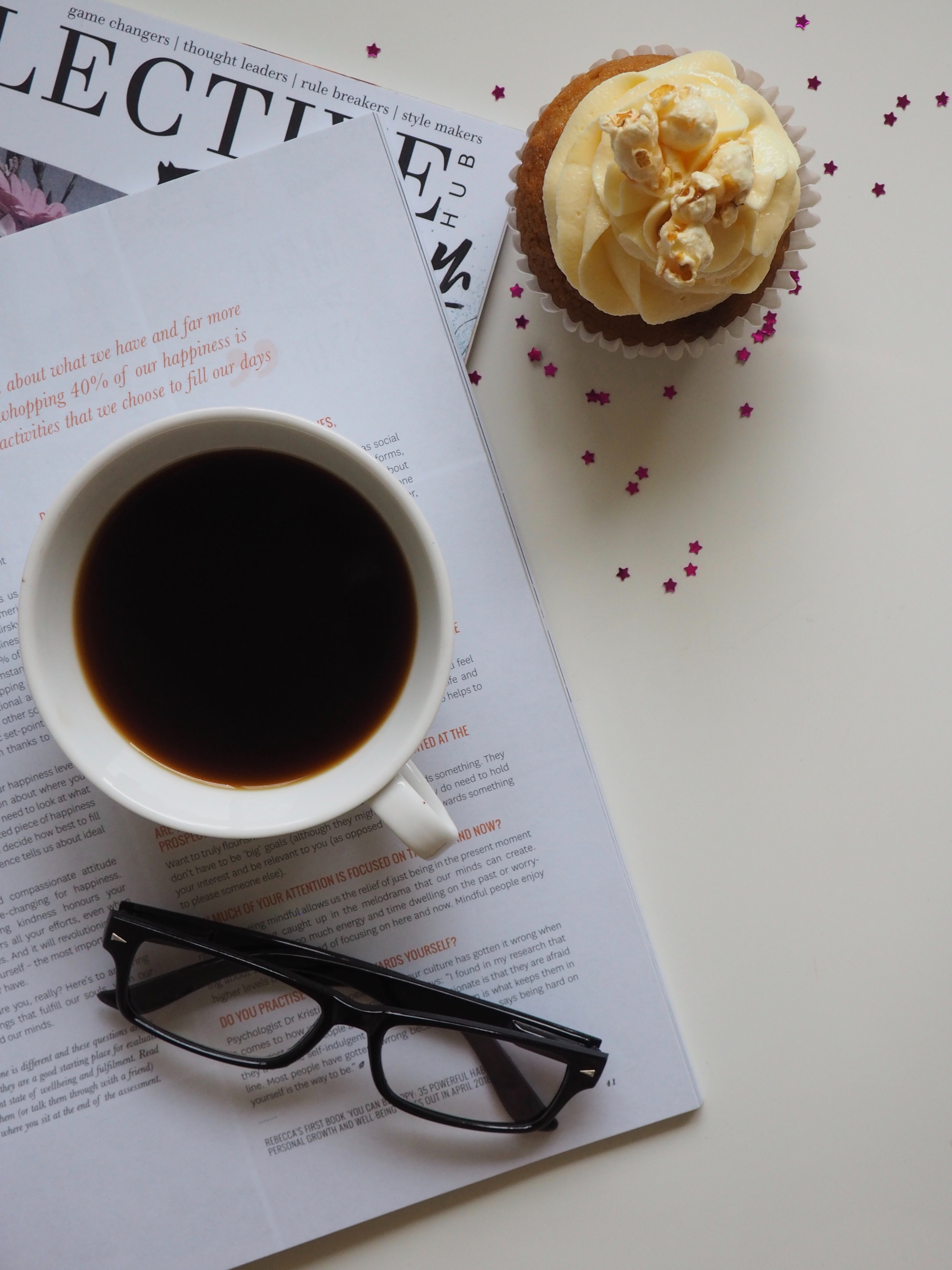 White ceramic cup with coffee on top of opened book and near eyeglasses photo