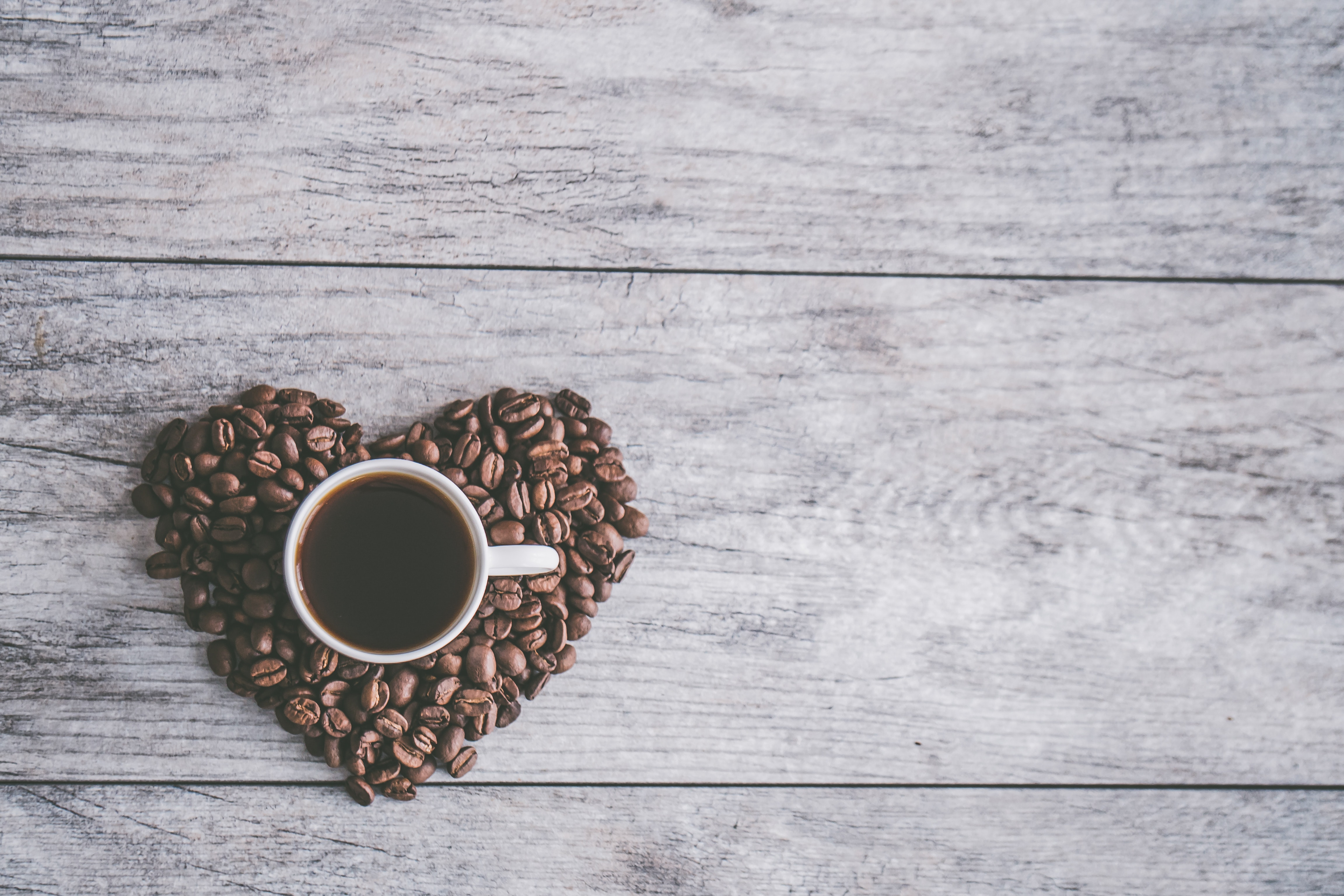 White Ceramic Mug Filled With Brown Liquid on Heart-shaped Coffee Beans, Background, Flatlay, Wood, Texture, HQ Photo