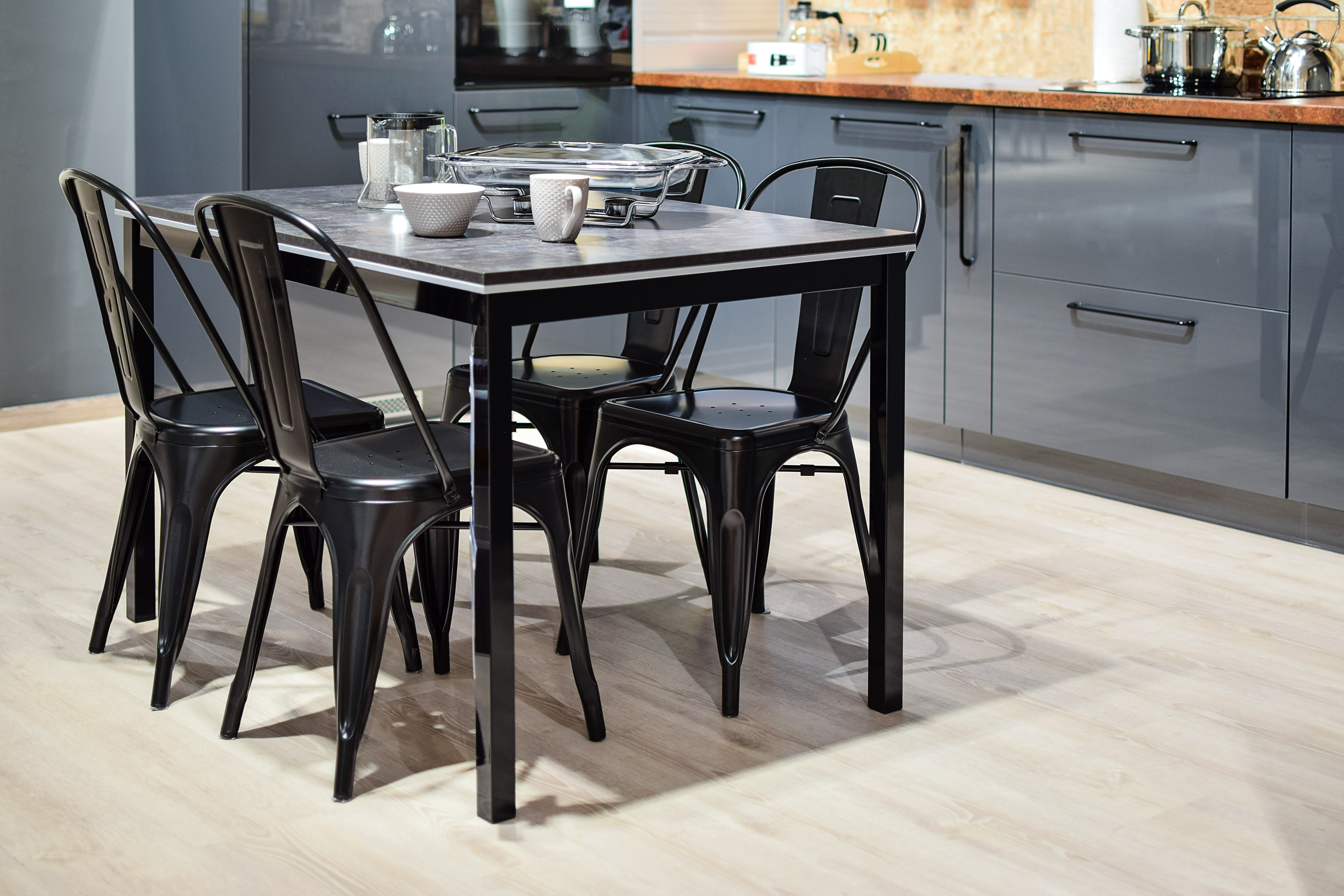 White ceramic mug on black dining table with four chair set photo