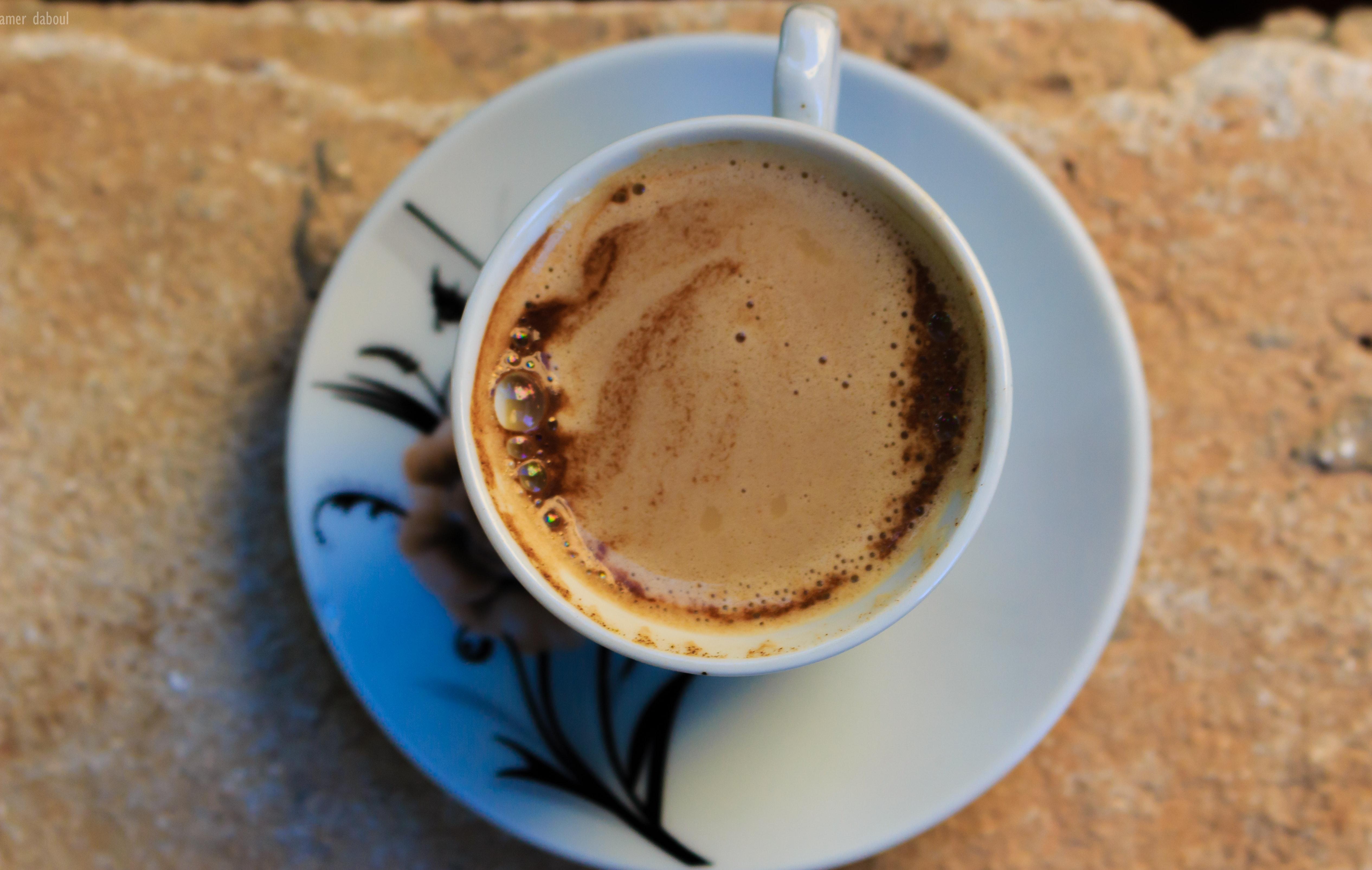 White ceramic mug with coffee and white ceramic saucer photo