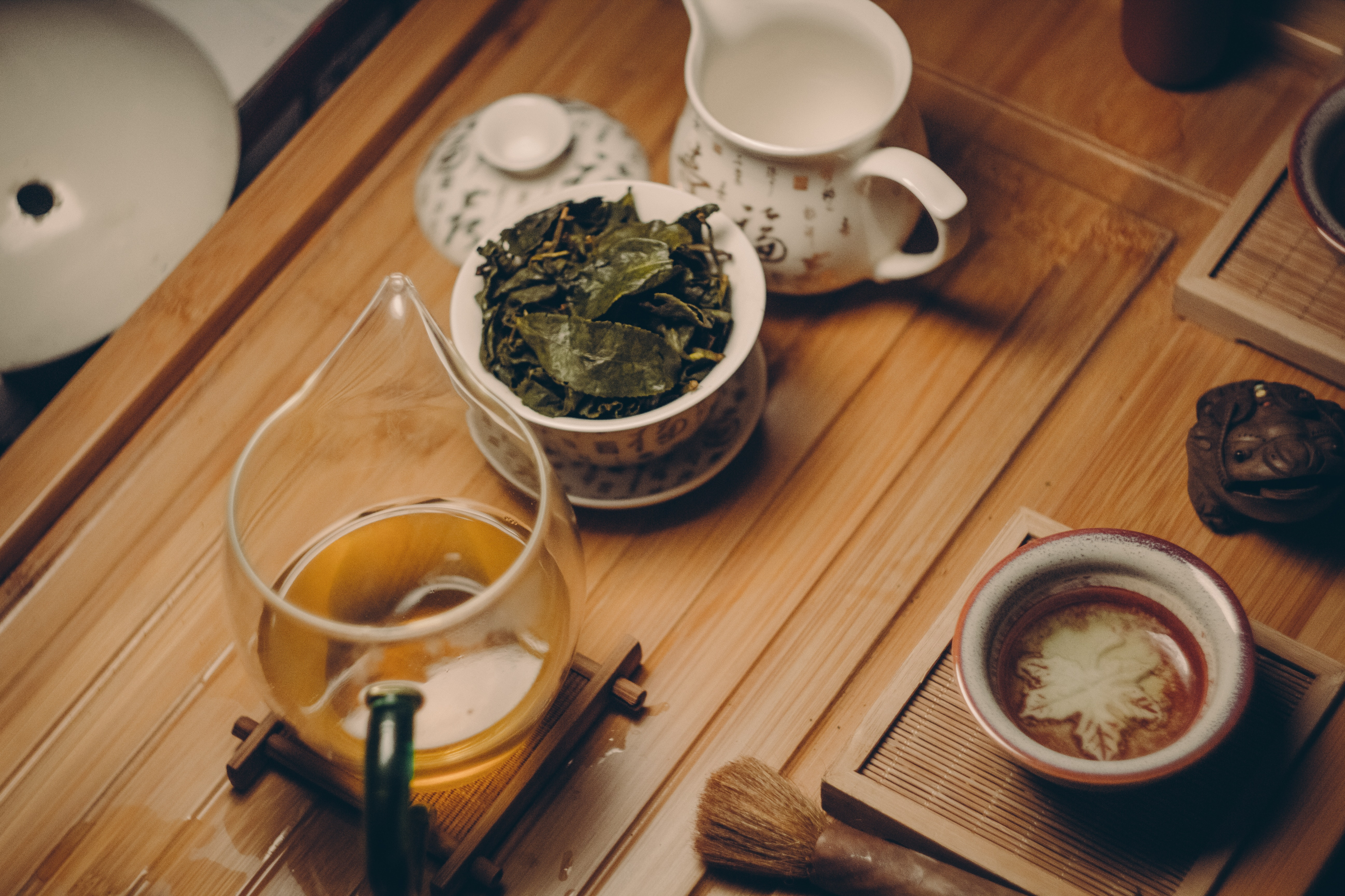 White ceramic teapot beside cup with leaves photo