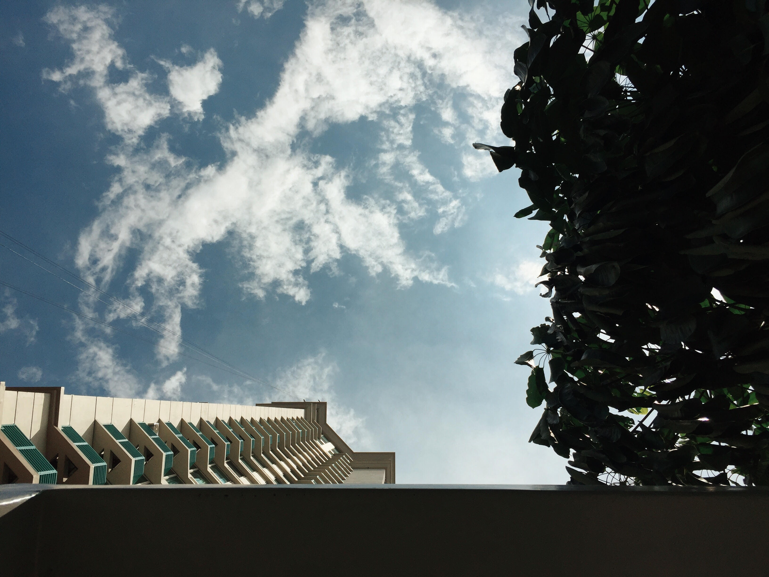 White concrete building with cloudy sky photo