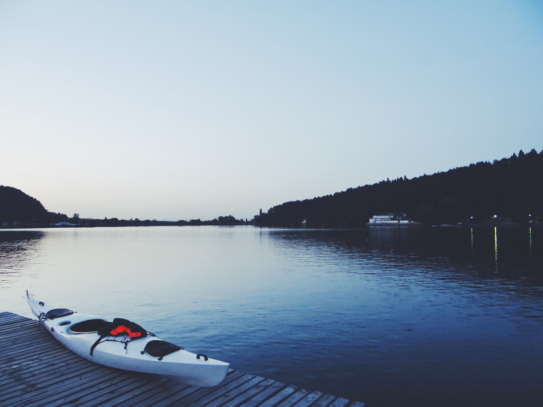 White kayak on brown wooden dock photo