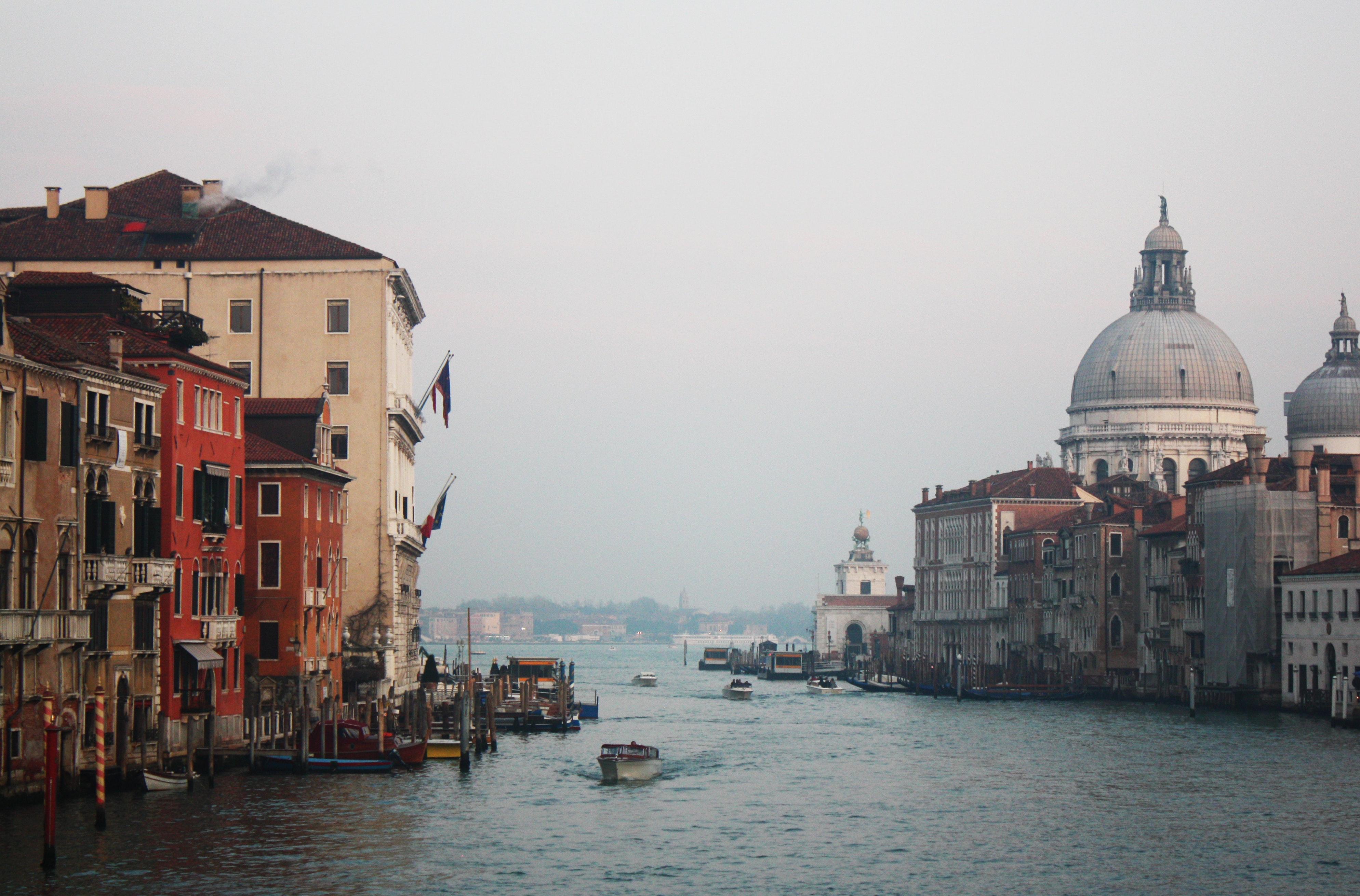 White motor boat on ocean beside concrete buildings photo