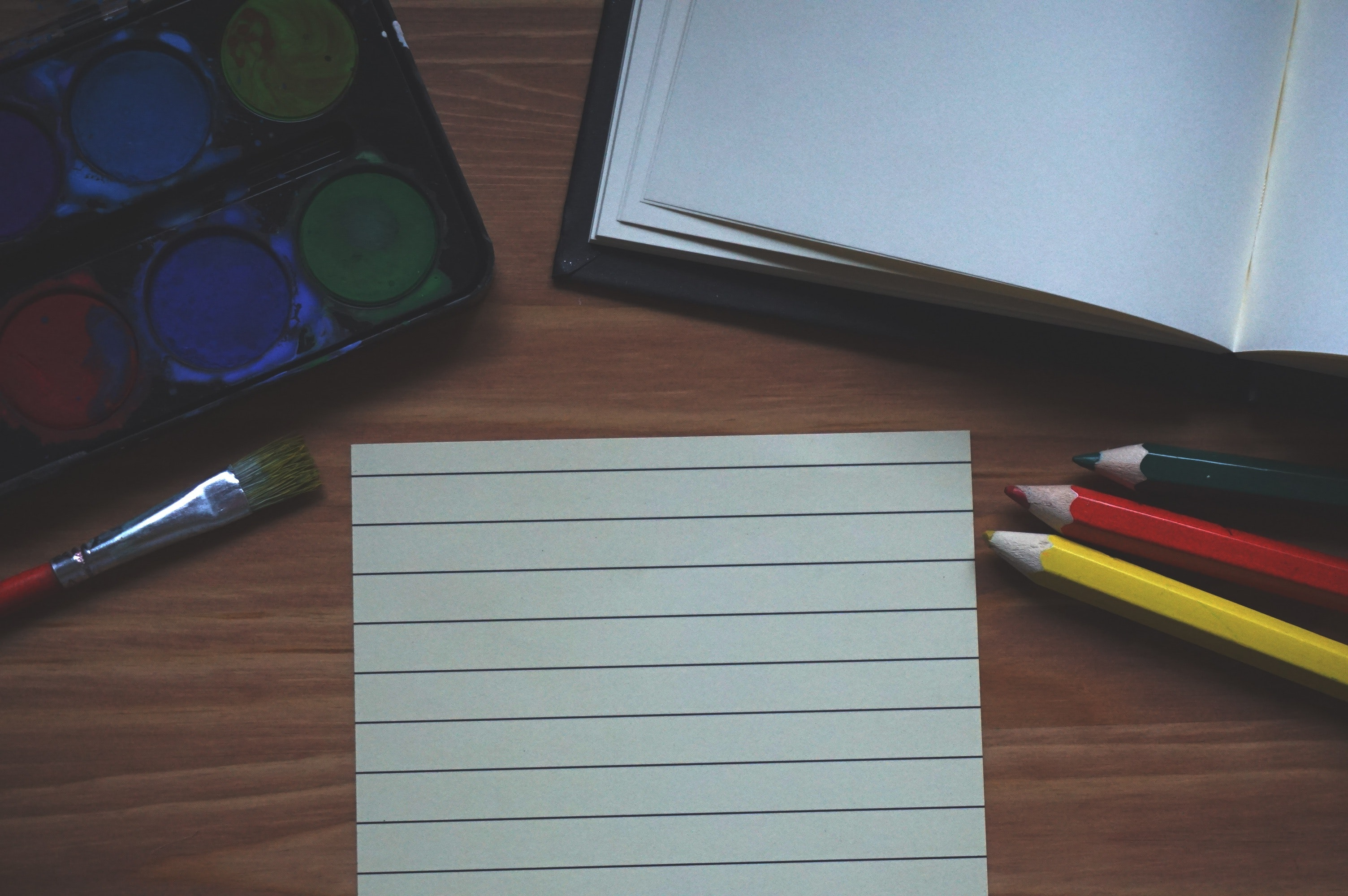 White ruled paper beside yellow colored pencil photo