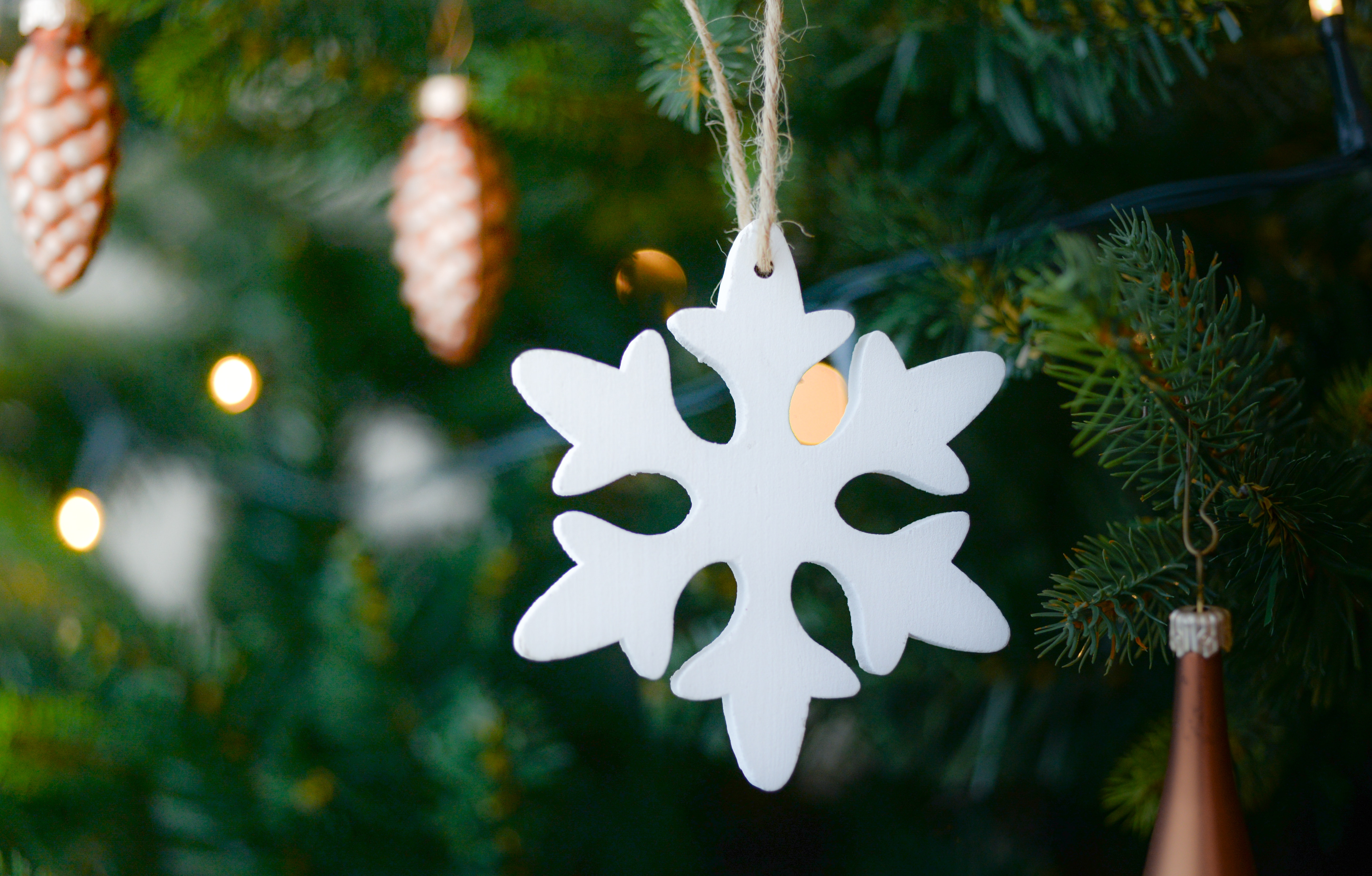 White snow flake hanging on christmas tree photo