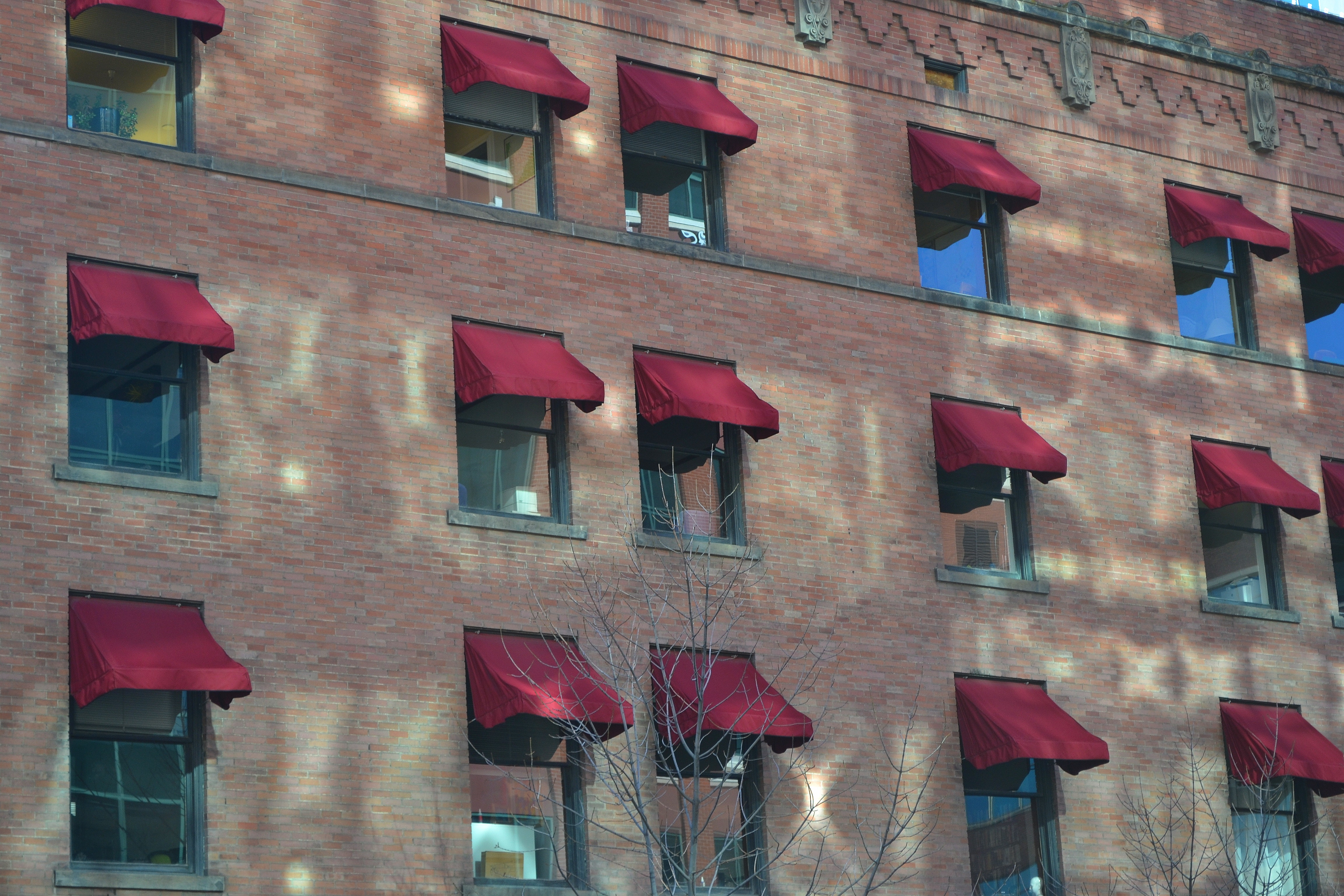 Windows with burgundy canopies along the brick wall of the building photo