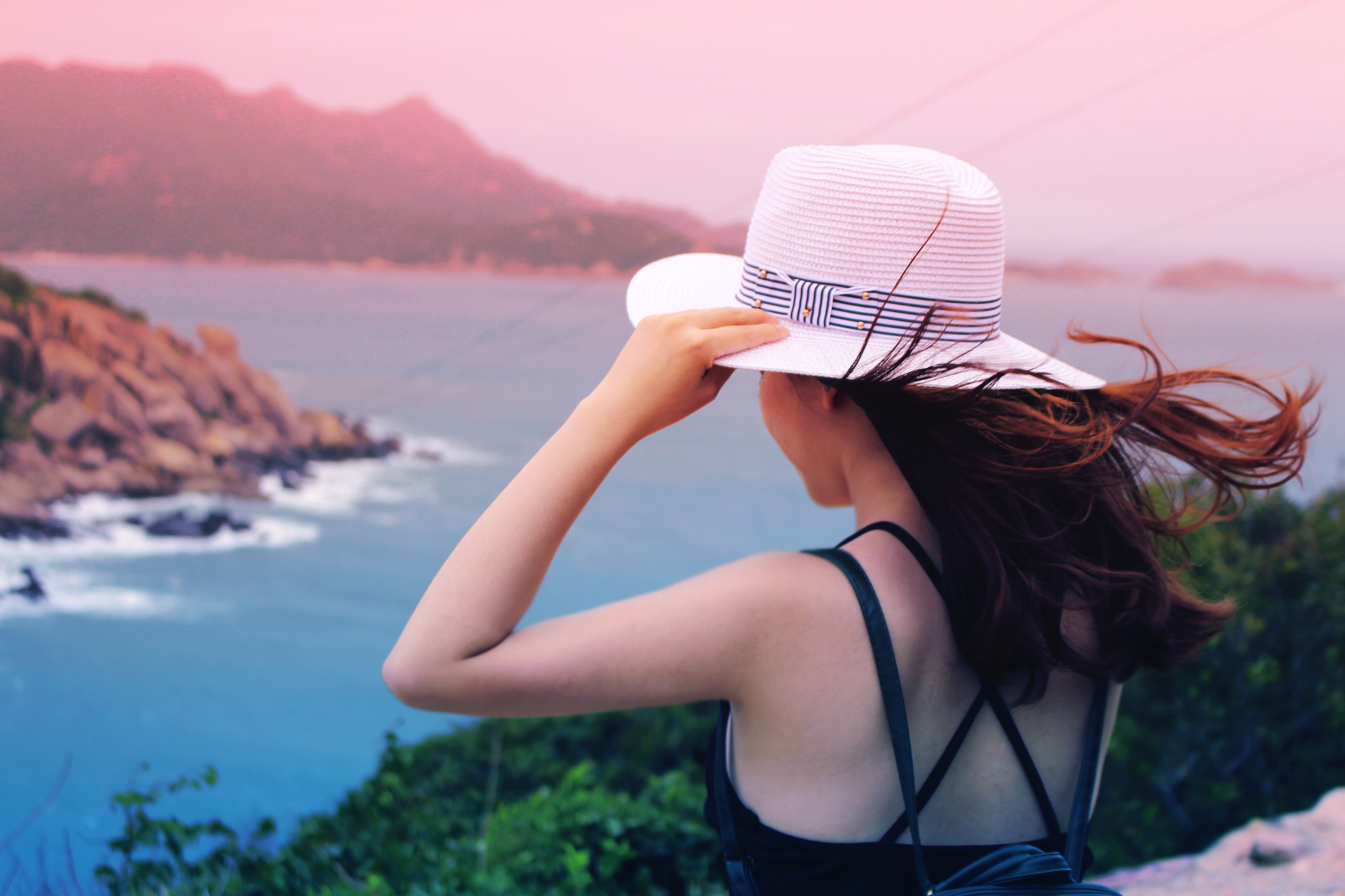 Wman holding wricker shade hat on ocean view photo