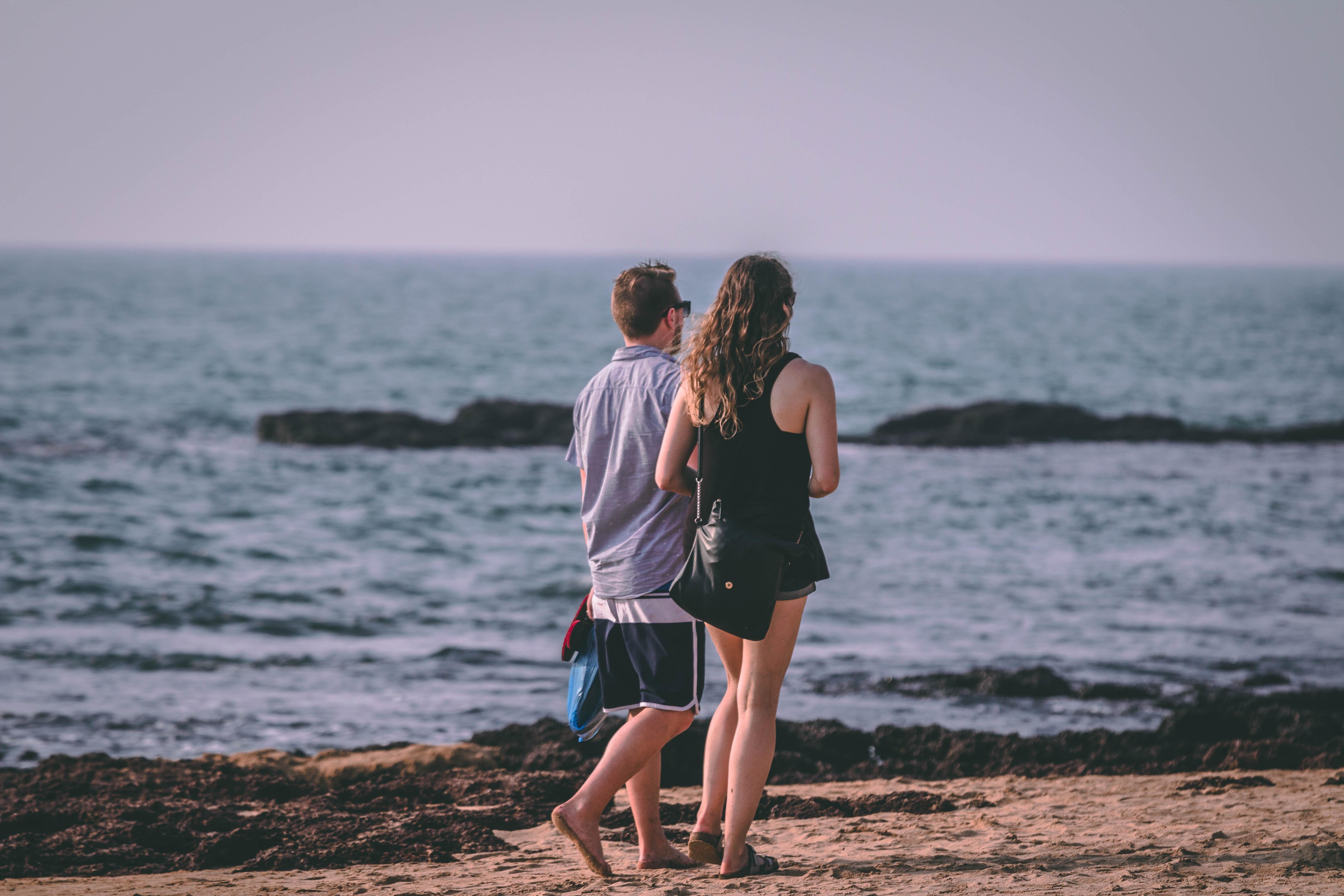 Woman and man walking near seashore photo