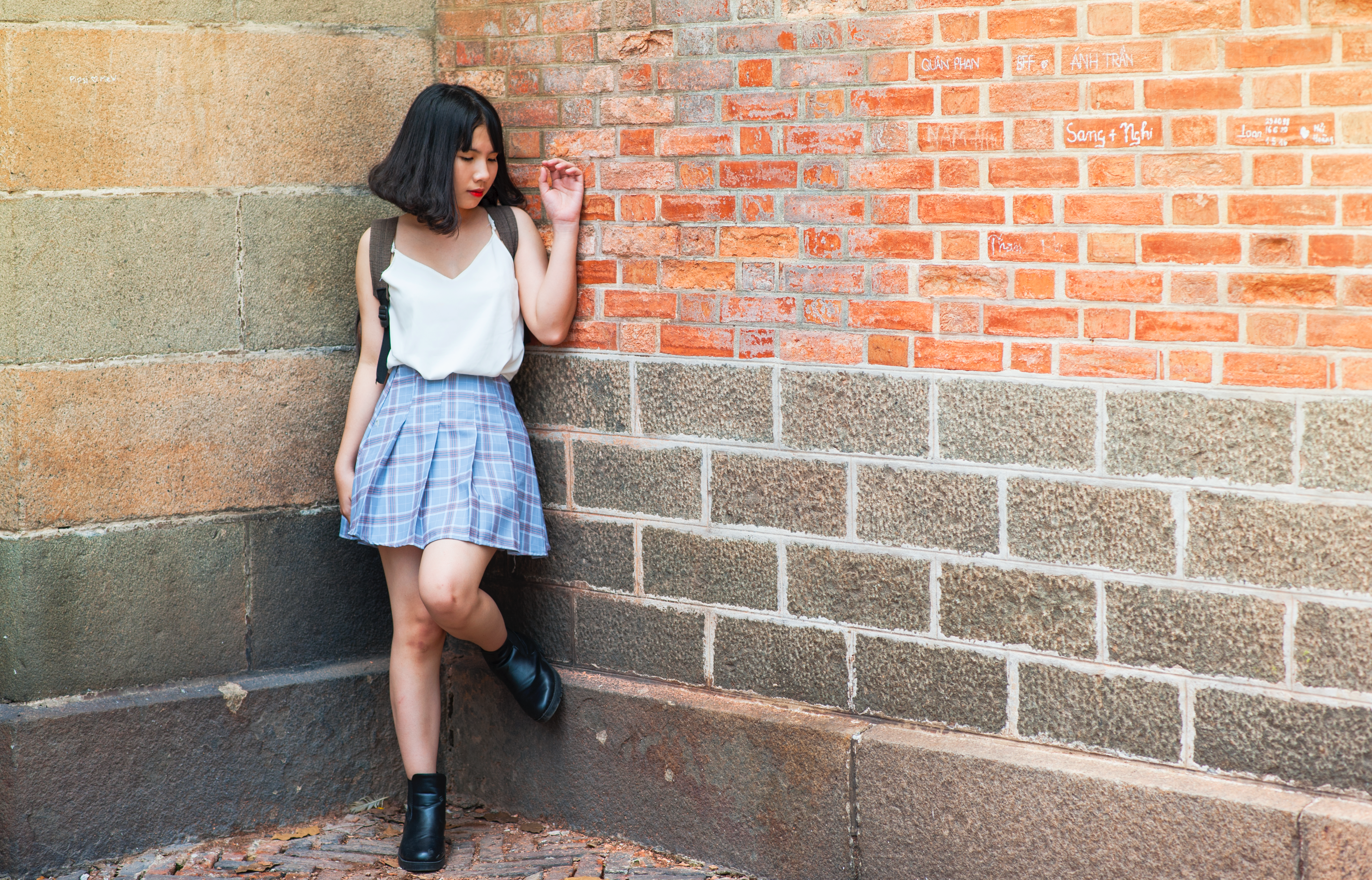 Woman beside brick and cinder wall photo