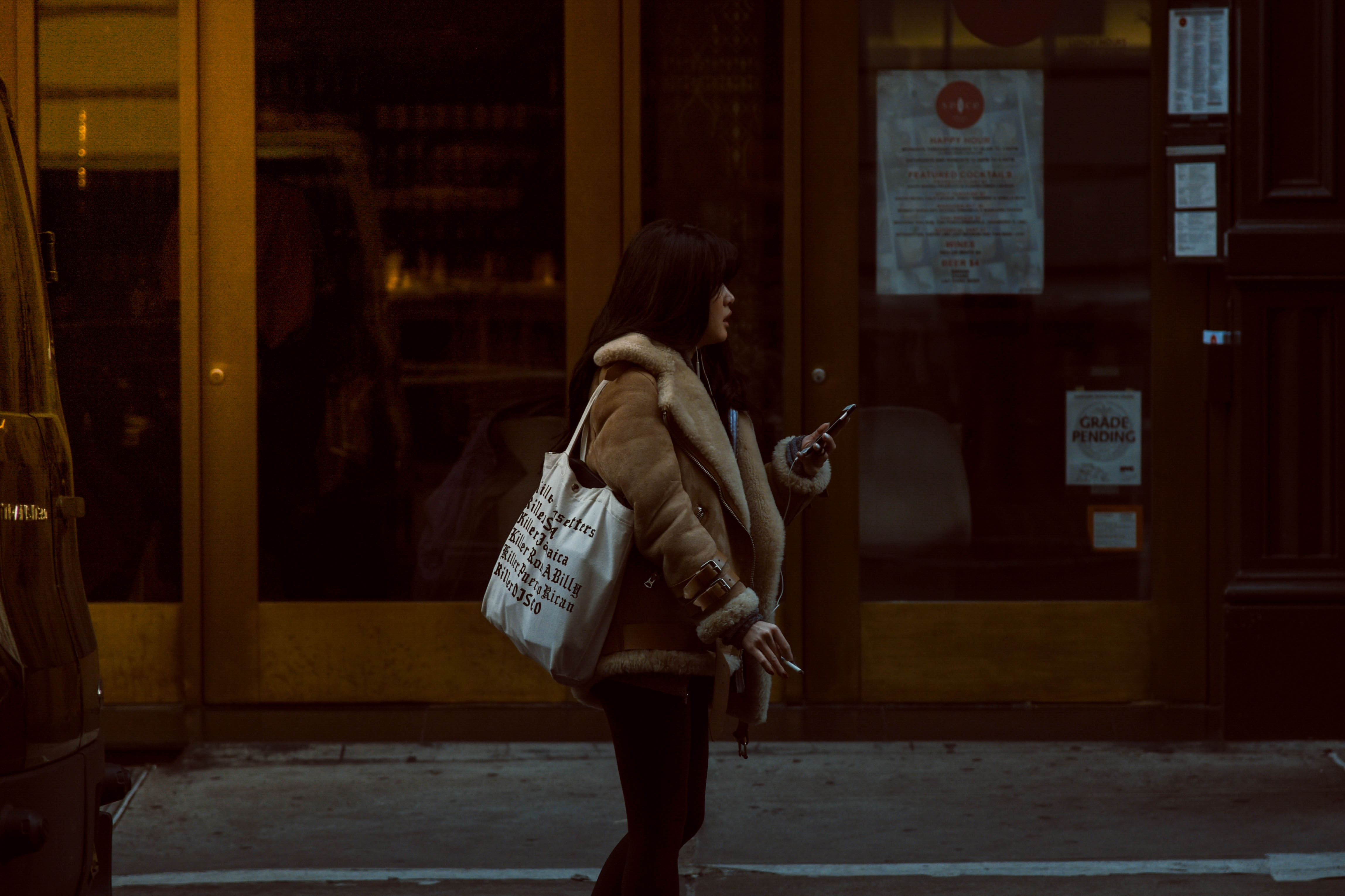 Woman carrying white tote standing beside brown glass door building photo