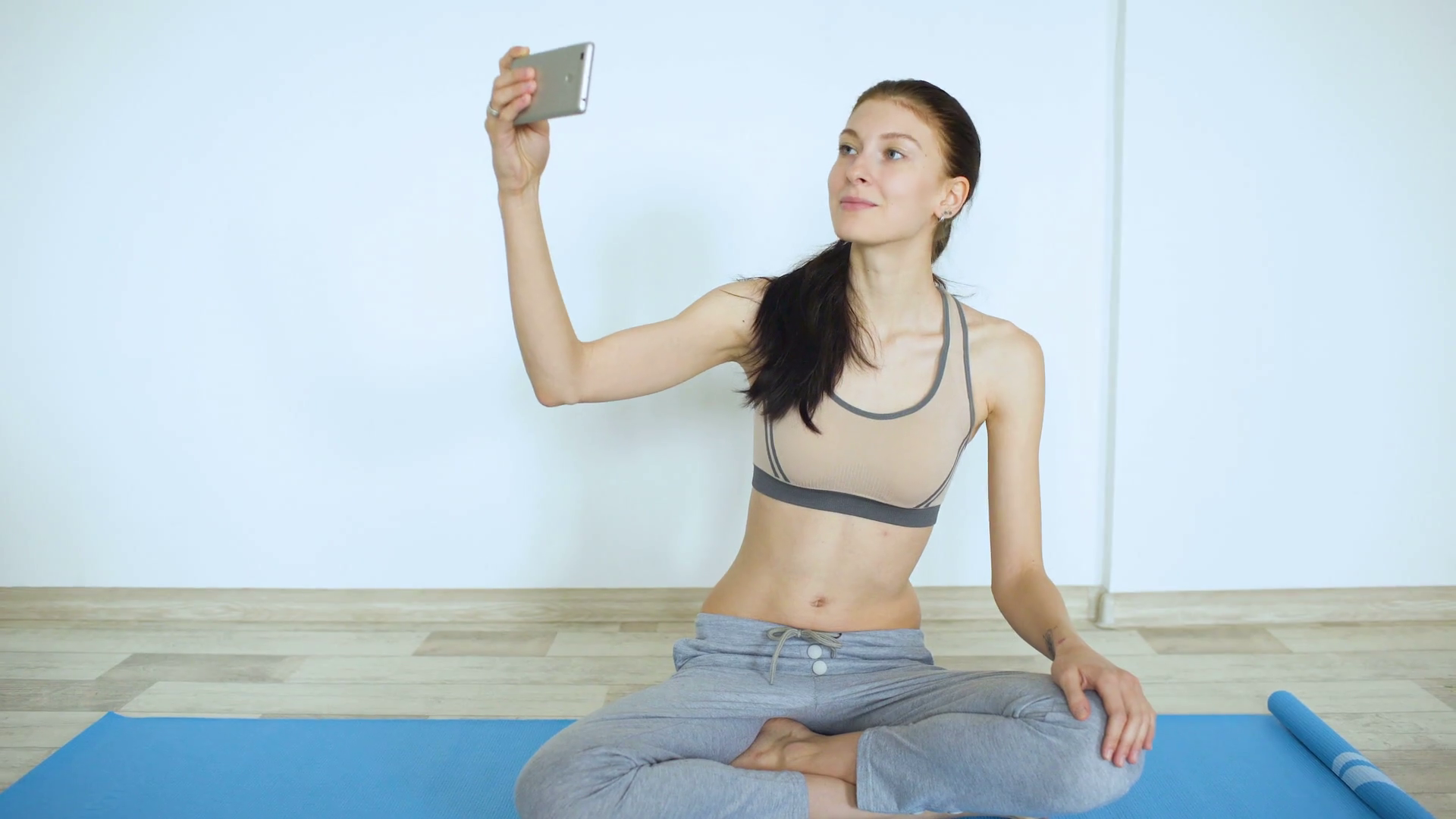 Young woman doing yoga exercise making selfie smile in smartphone ...