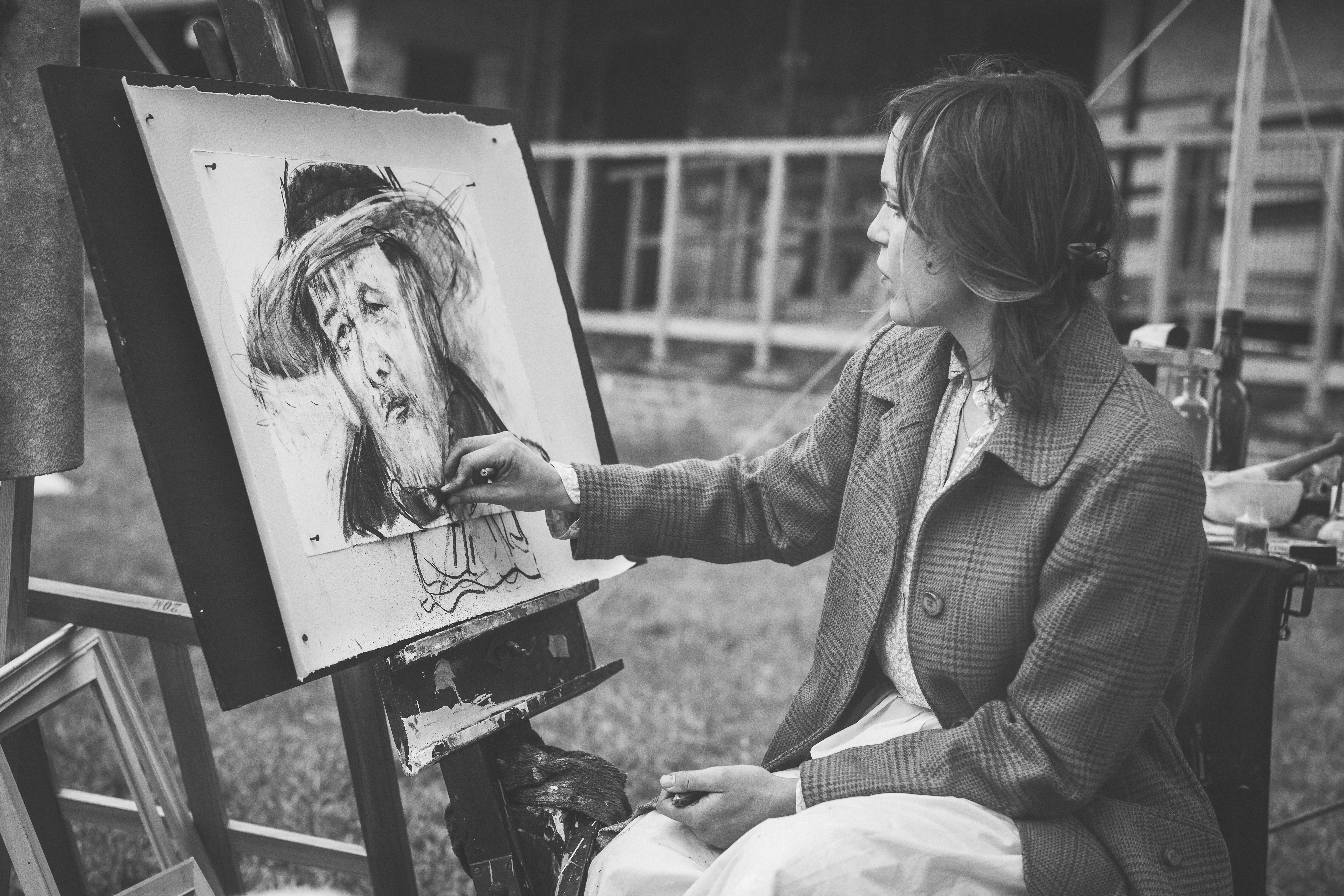 Woman drawing a man with hat photo