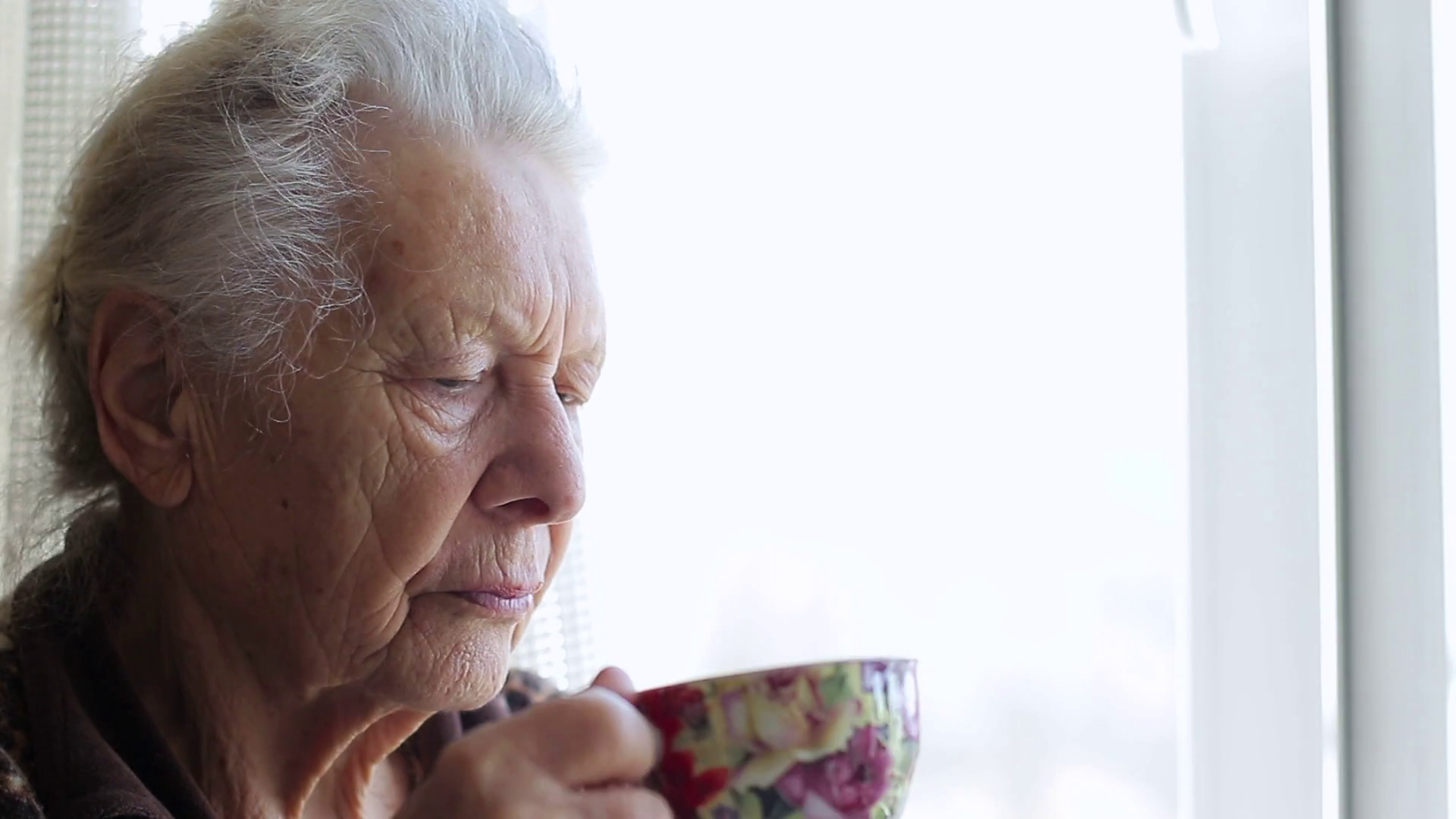 Sad woman drinking tea by the window Stock Video Footage - Videoblocks