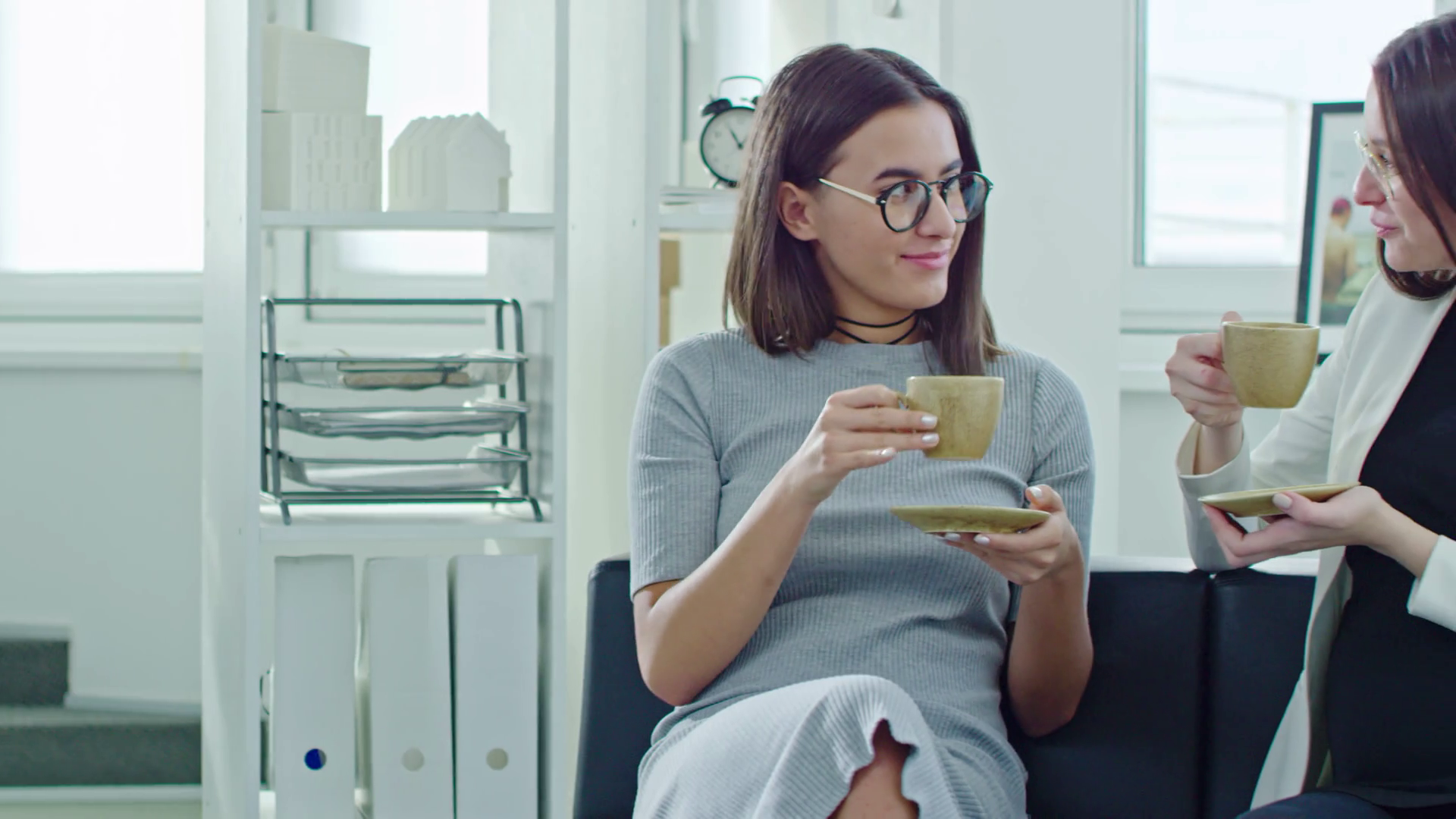 PAN of woman in glasses drinking tea and chatting with her pregnant ...
