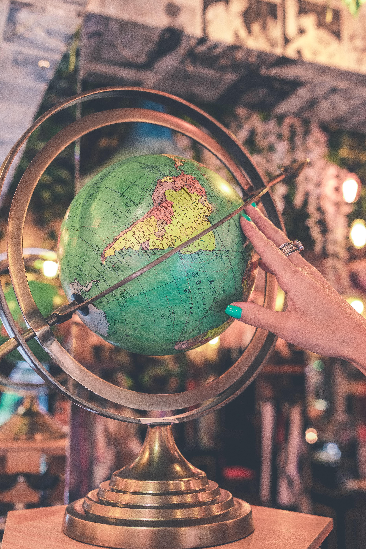Woman Hand Touches Green Desk Globe, Lights, Latitude, Longitude, Map, HQ Photo